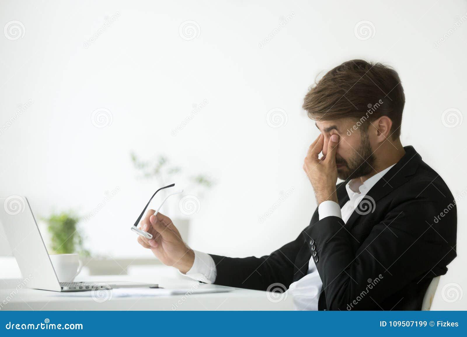 Ögon tröttar ut på arbete, den trötta utmattade affärsmannen som av tar gla