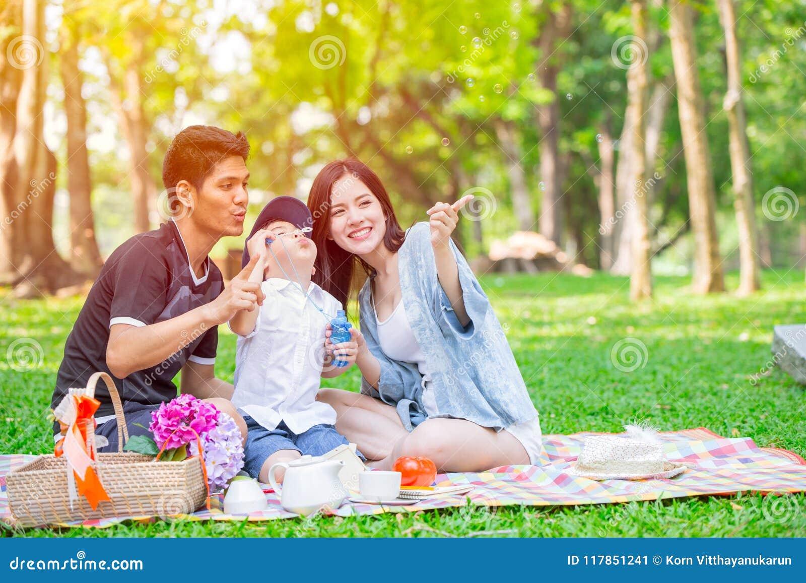 Ögonblick för picknick för ferie för asiatisk tonårig unge för familj en lyckligt i parkera
