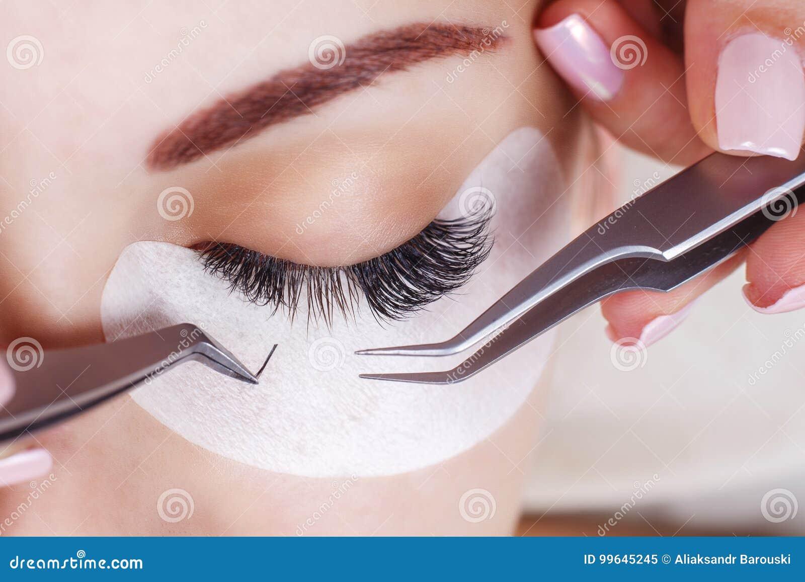 Ögonfransförlängningstillvägagångssätt Kvinnan synar med långa ögonfranser Snärtar slut upp, makro, selektiv fokus