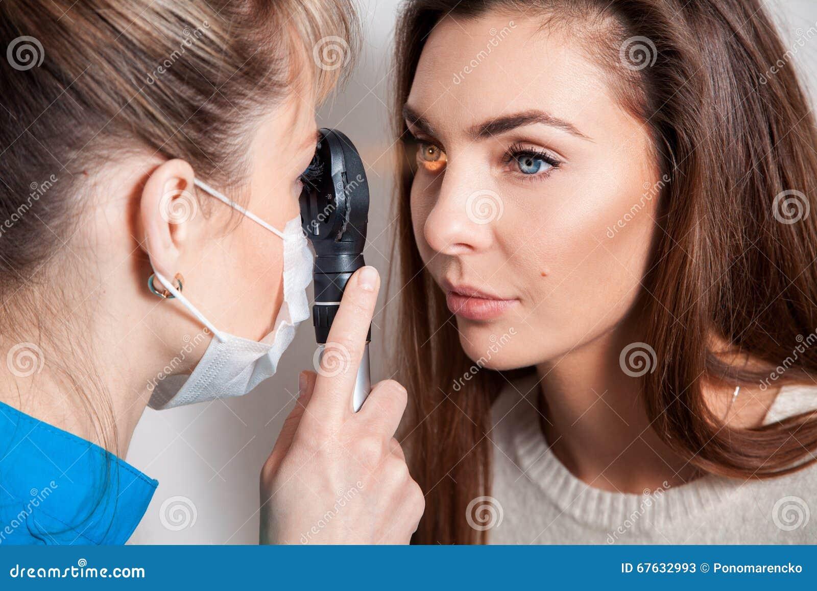 Ögonläkaren undersöker ögonen genom att använda en ögon- apparat