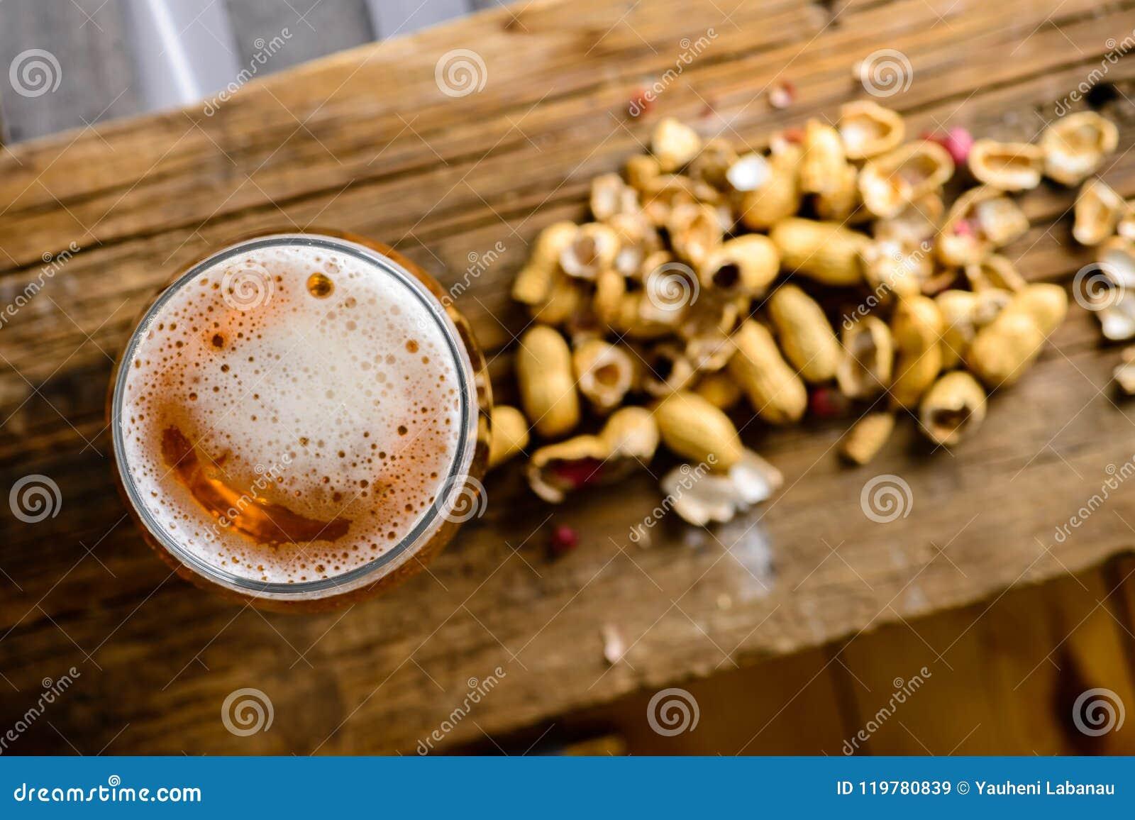 Ölexponeringsglas med mörkt kallt öl med bubblafradga och jordnötter på