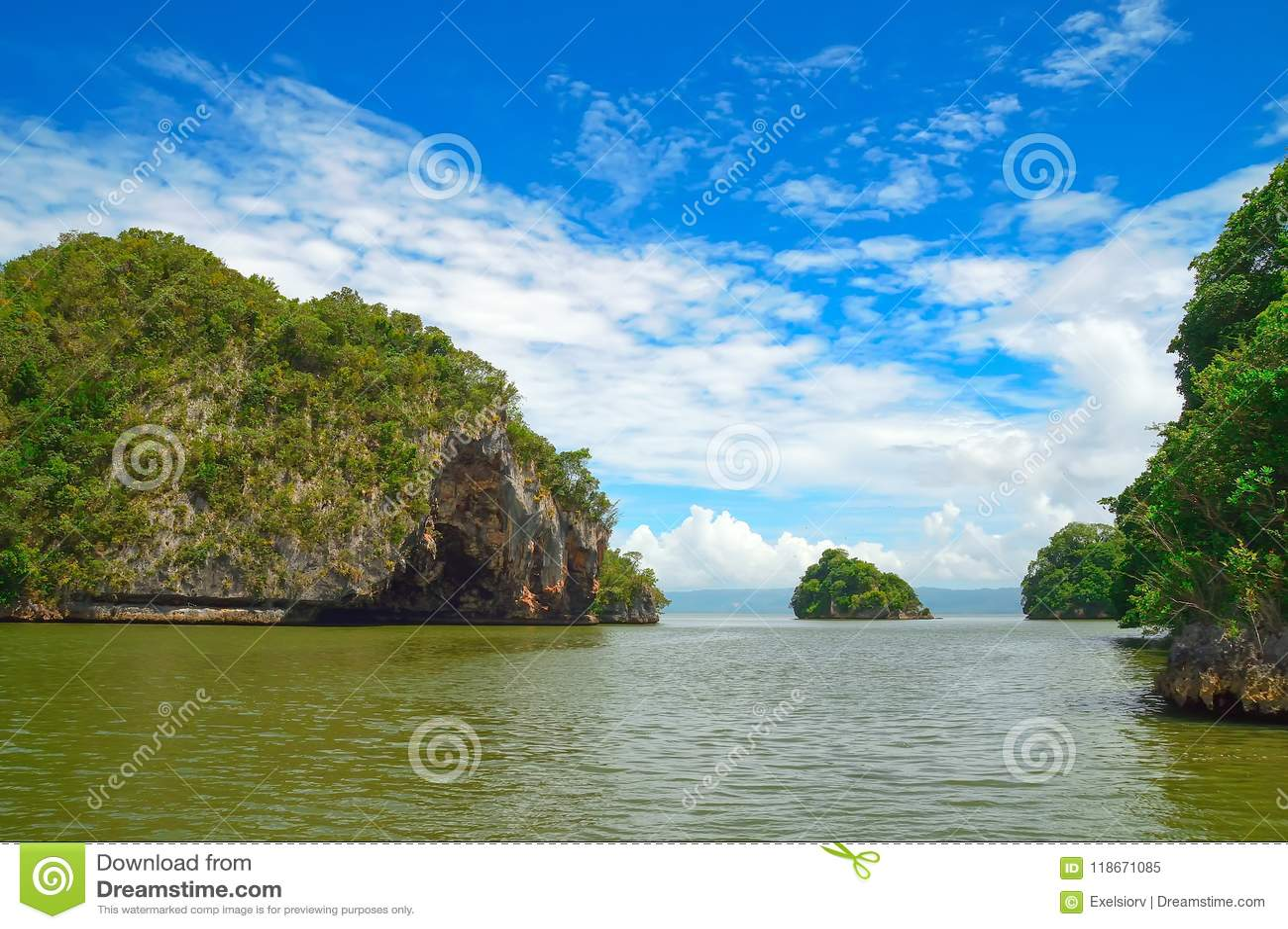 Ön vaggar i Atlanticet Ocean som täckas med grön vegetation, mot en bakgrund av kusten i bakgrunden Los