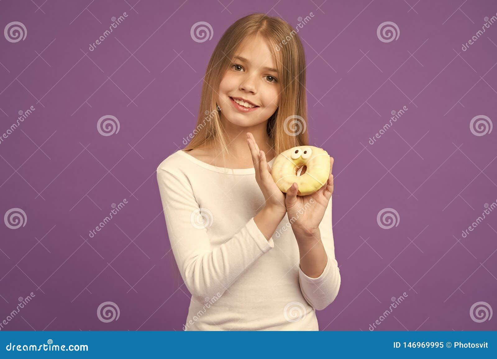 Önskar du en lycklig unge för tugga med skräpmat Barnleende med munken p? violett bakgrund Liten flicka med den glasade cirkeln