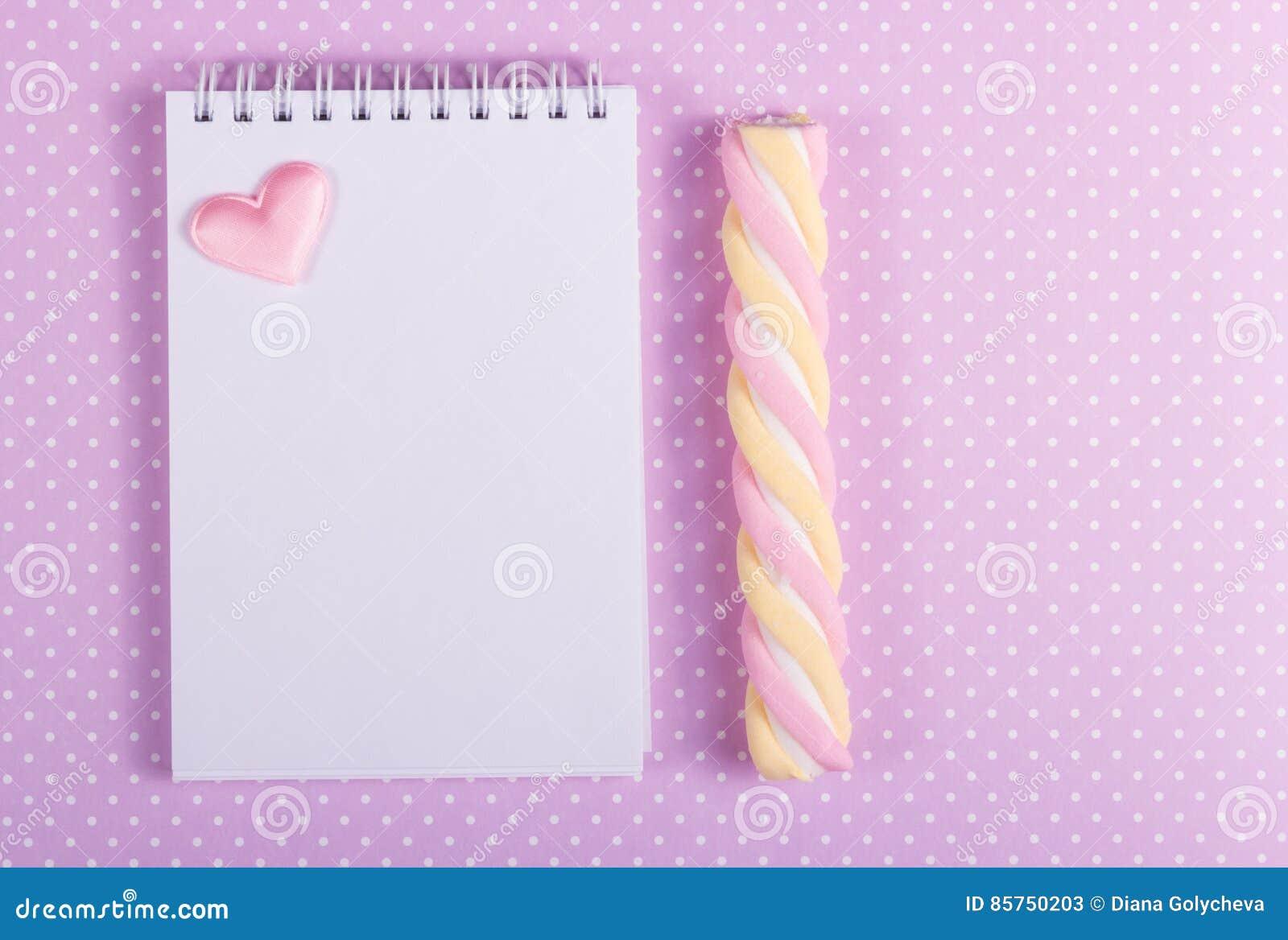 Öppen anteckningsbok med en tom sida, en marshmallowpinne och en liten valentin på en bakgrund av pricken