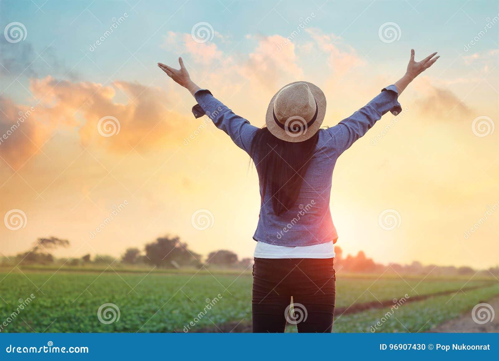 Öppen armandedräkt för kvinna av ny luft under solnedgången på ängen