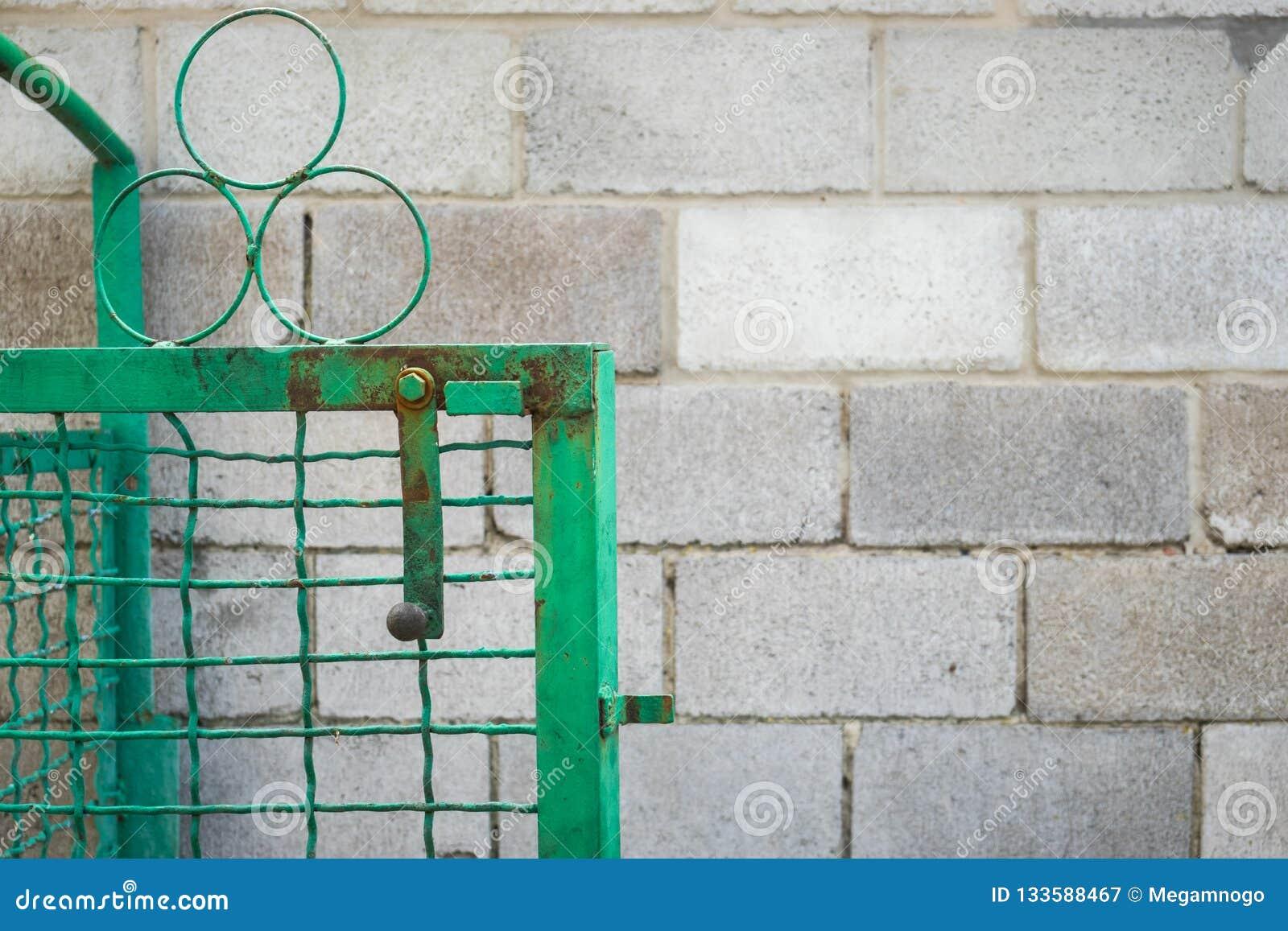 Öppen grön port och staket för svetsat ingrepp mot en vägg av askakvarteret