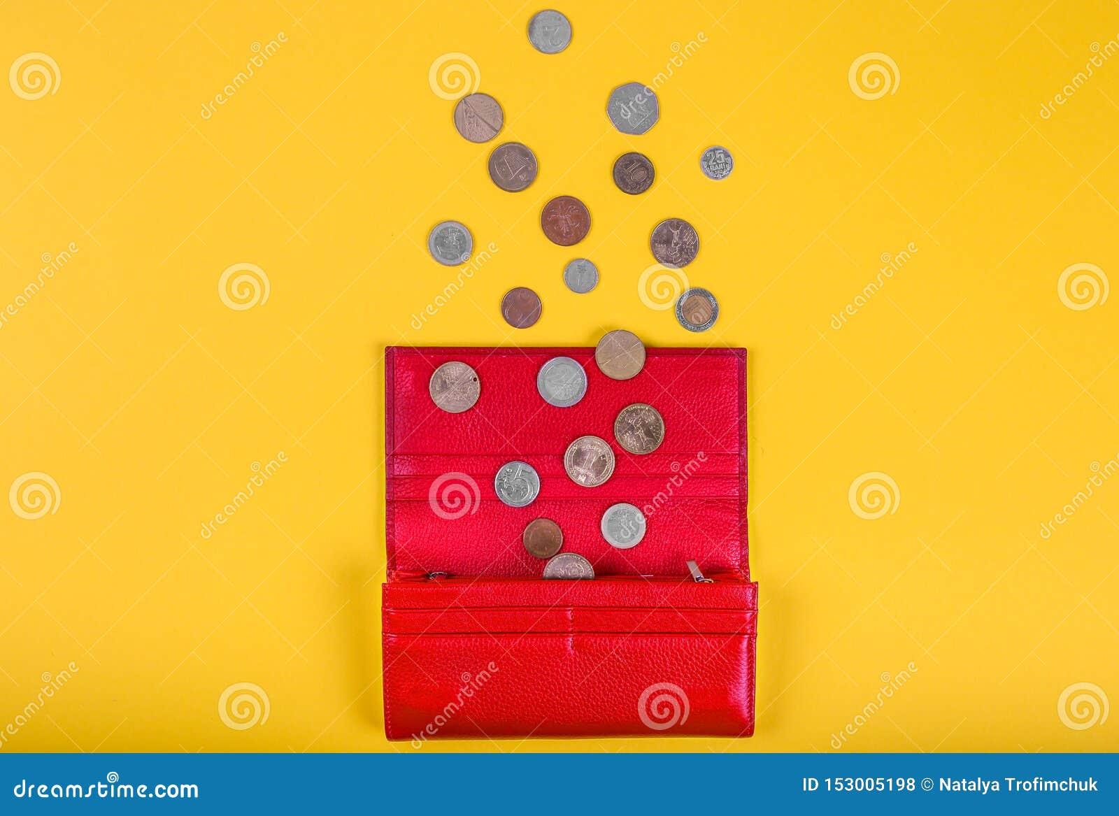 Öppen kvinnlig röd läderplånbok med olika mynt på gul bakgrund med kopieringsutrymme, över huvudet sikt