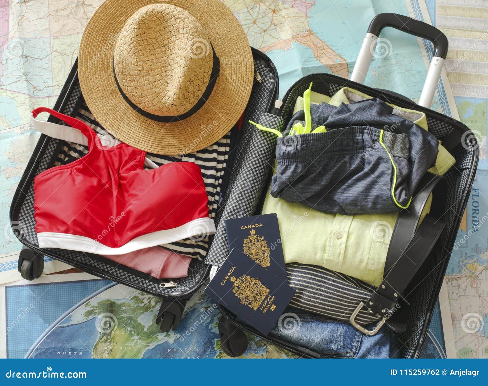 Öppen påse för handelsresande` s med kläder, tillbehör och passet Lopp- och semesterbegrepp