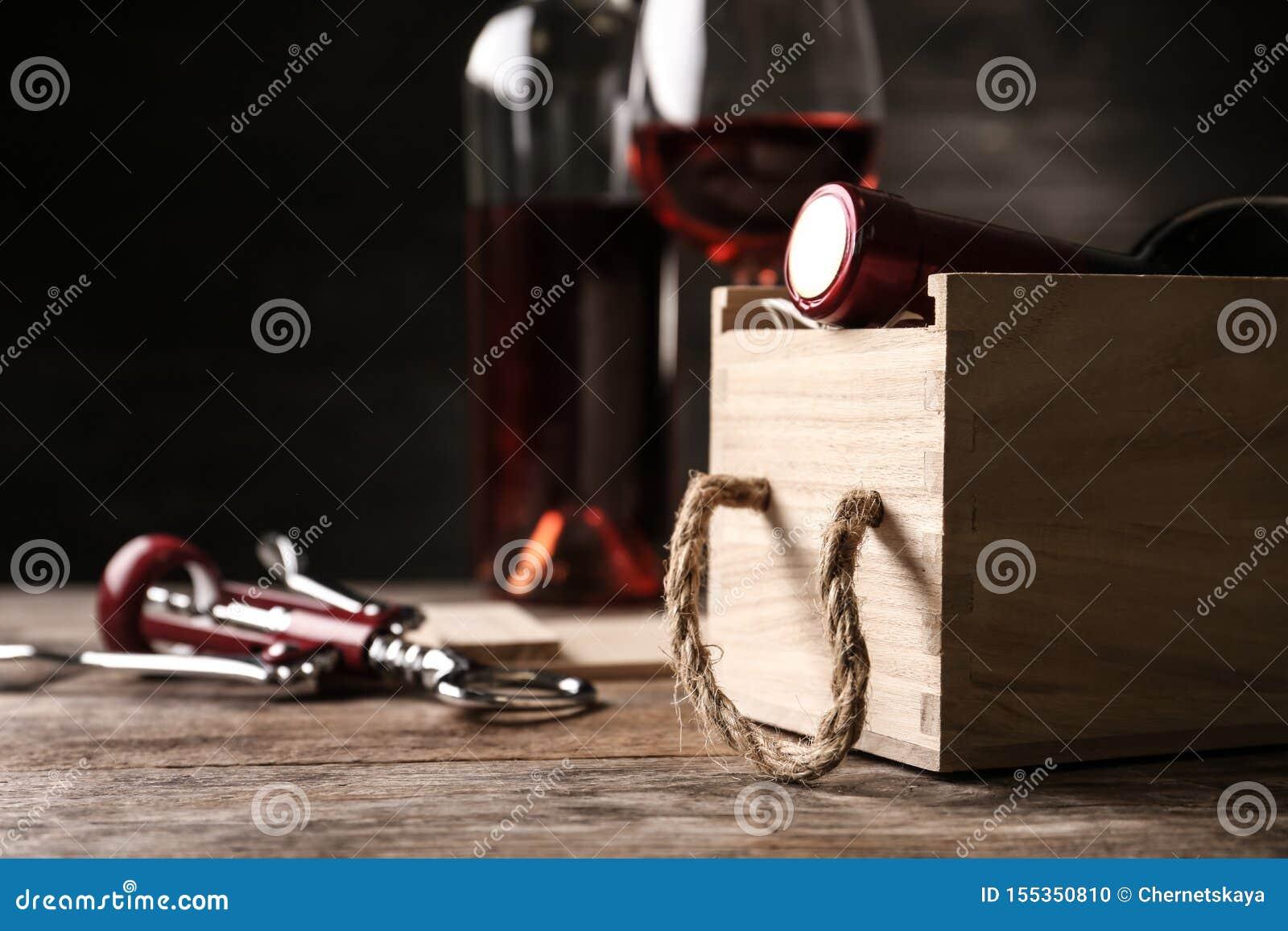 Öppen träspjällåda med flaskan av vin och korkskruvet på tabellen