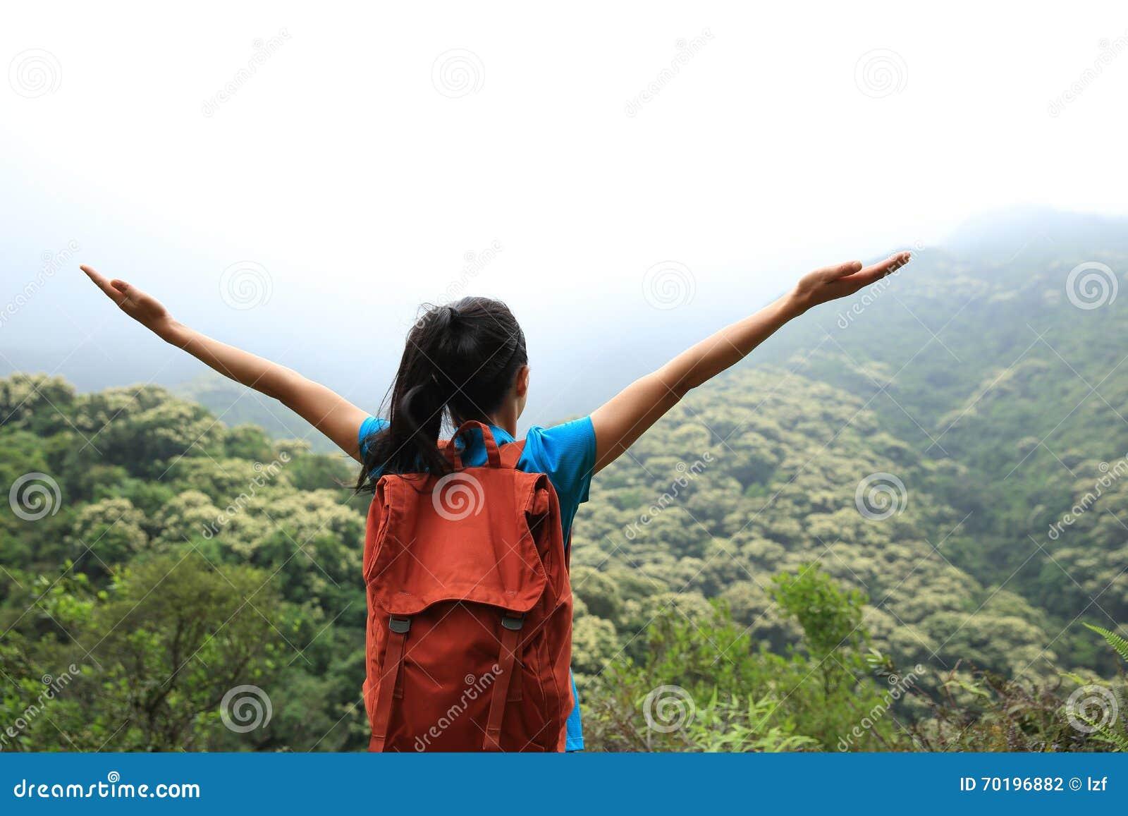 Öppna armar för ung asiatisk kvinna till vårskogen
