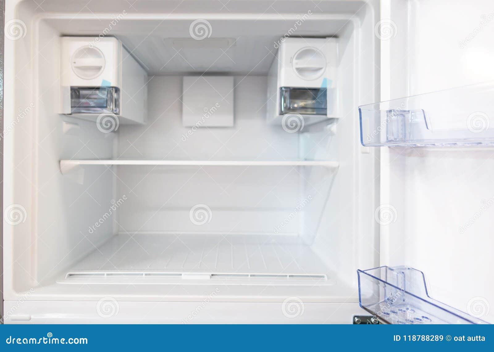 Öppna det tomma nya vita kylskåpet inom kylen med hyllor