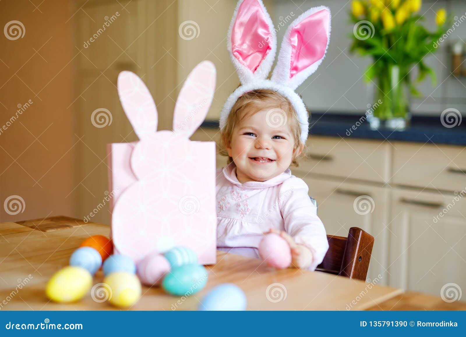 Öron för kanin för påsk för gullig liten litet barnflicka som bärande spelar med kulöra pastellfärgade ägg Lyckligt behandla som