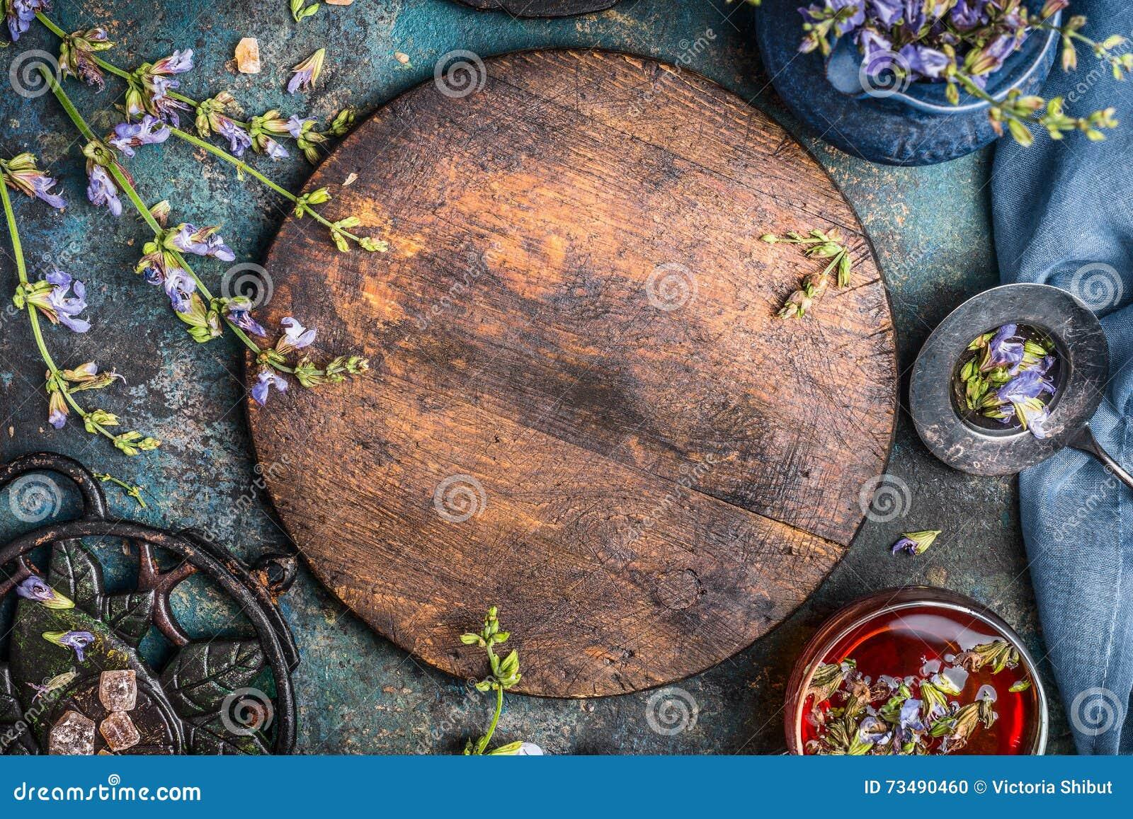 Örttebakgrund med det runda träbrädet, kopp te och olika blommor och läkaörter på mörk bakgrund, bästa sikt, fram