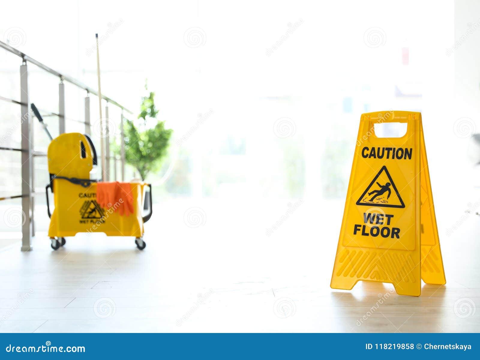 Ösregnar det VÅTA GOLVET för uttrycksVARNINGEN på säkerhetstecken och den gula golvmoppet med lokalvårdtillförsel, inomhus