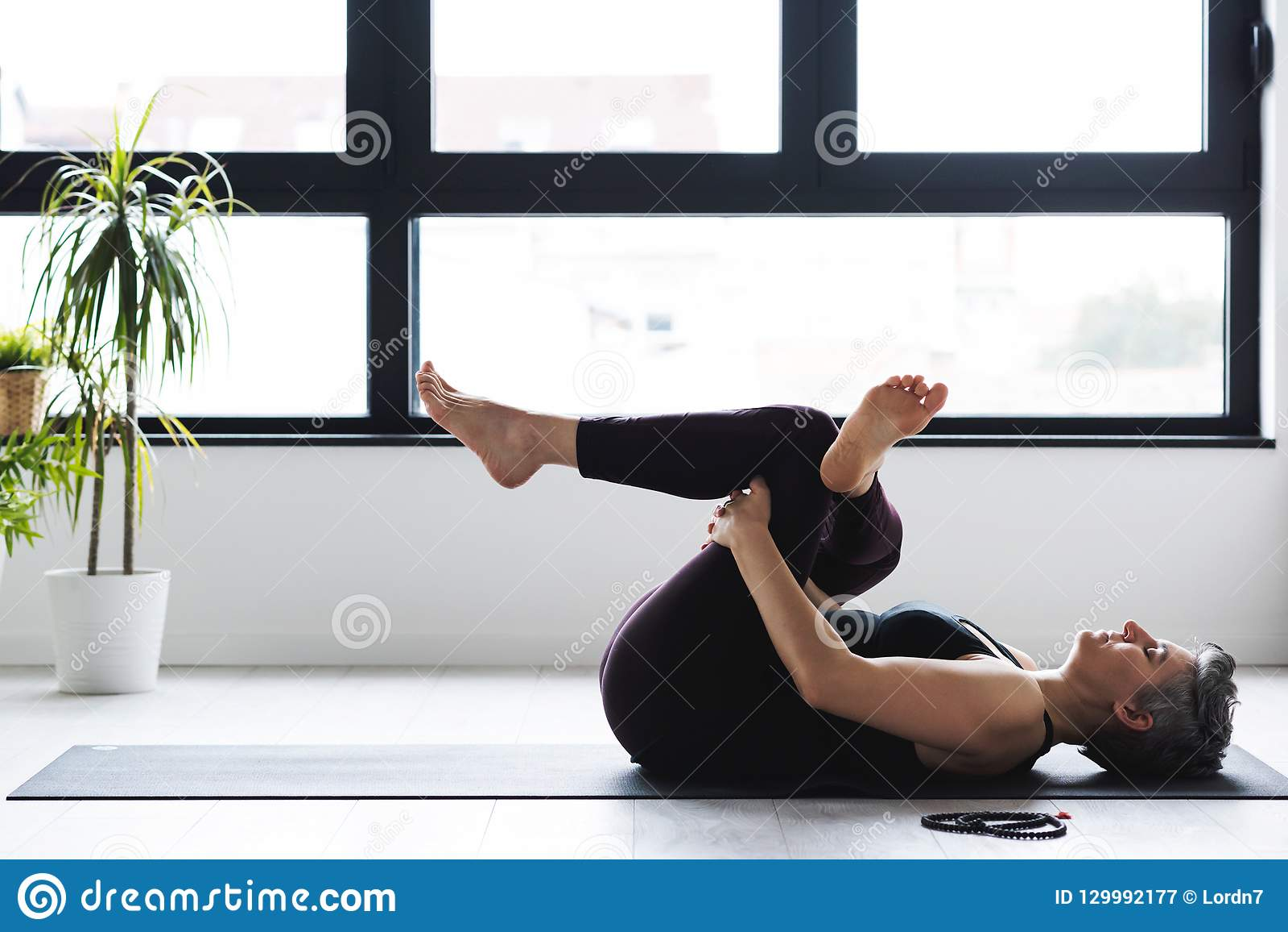 Övande yoga för mogen Caucasian kvinna på livingroomgolv