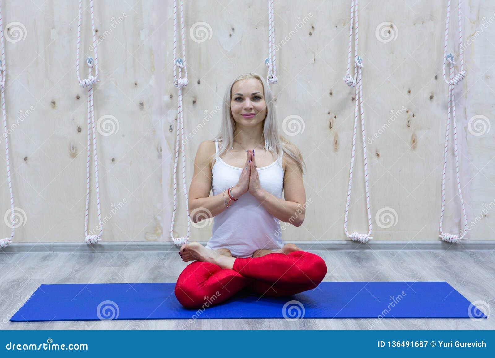 Övande yoga för ung attraktiv kvinna som sitter i den Padmasana övningen