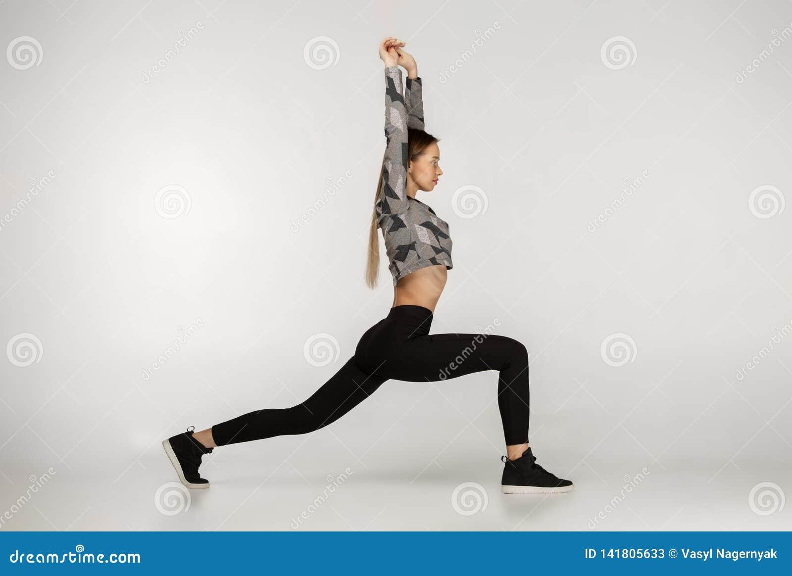 Övande yoga för ung sportig attraktiv kvinna som gör omvänd krigareövning