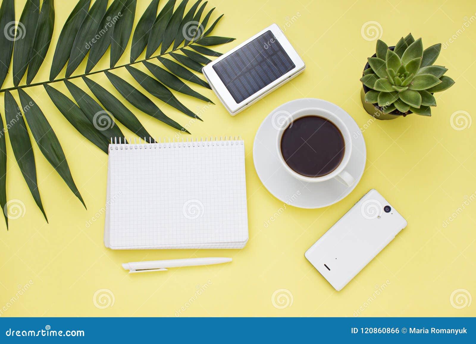Över huvudet affärsram med ett sol- batteri, en telefon och en kopp kaffe Top beskådar