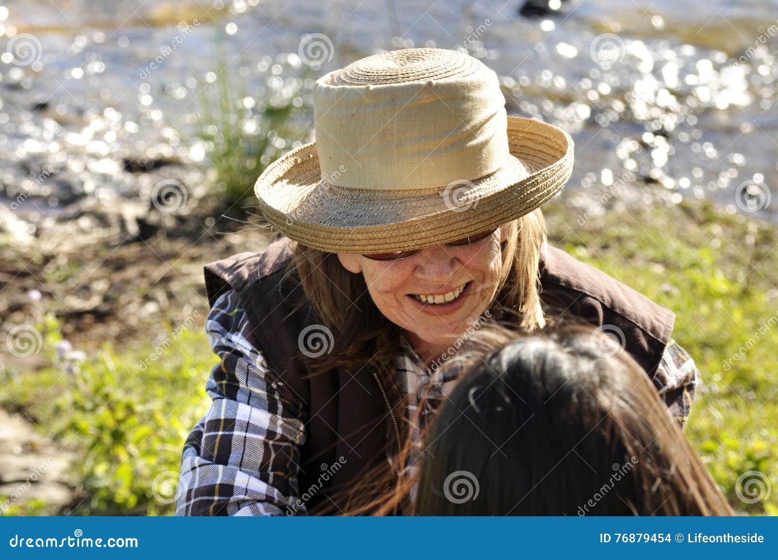 Över huvudet sikt av den medelåldersa kvinnan i konversation som ler med vännen