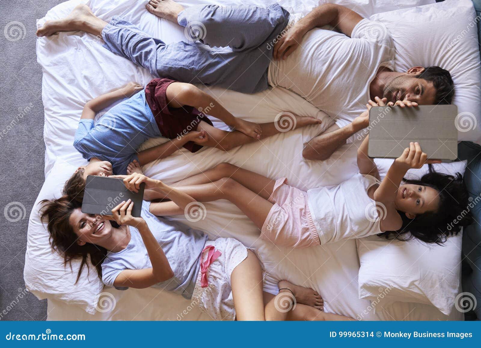 Över huvudet sikt av familjen som ligger på säng genom att använda Digital minnestavlor