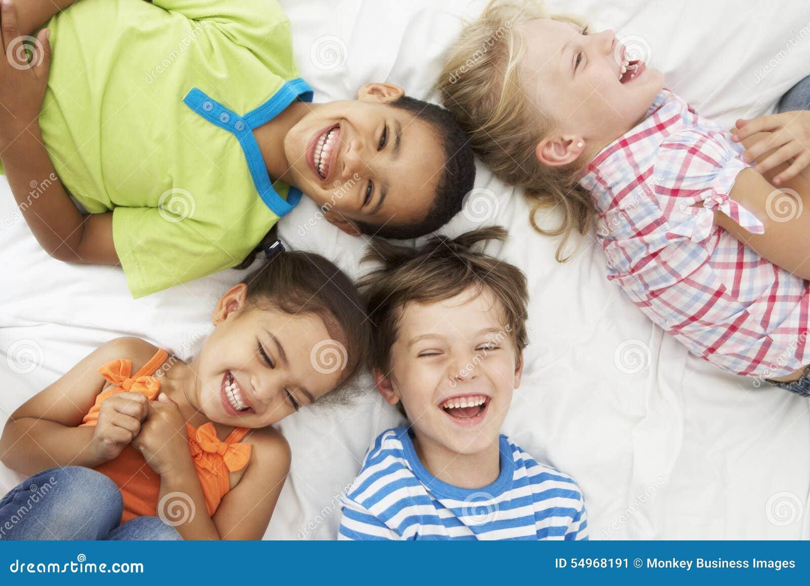 Över huvudet sikt av fyra barn som spelar på säng tillsammans