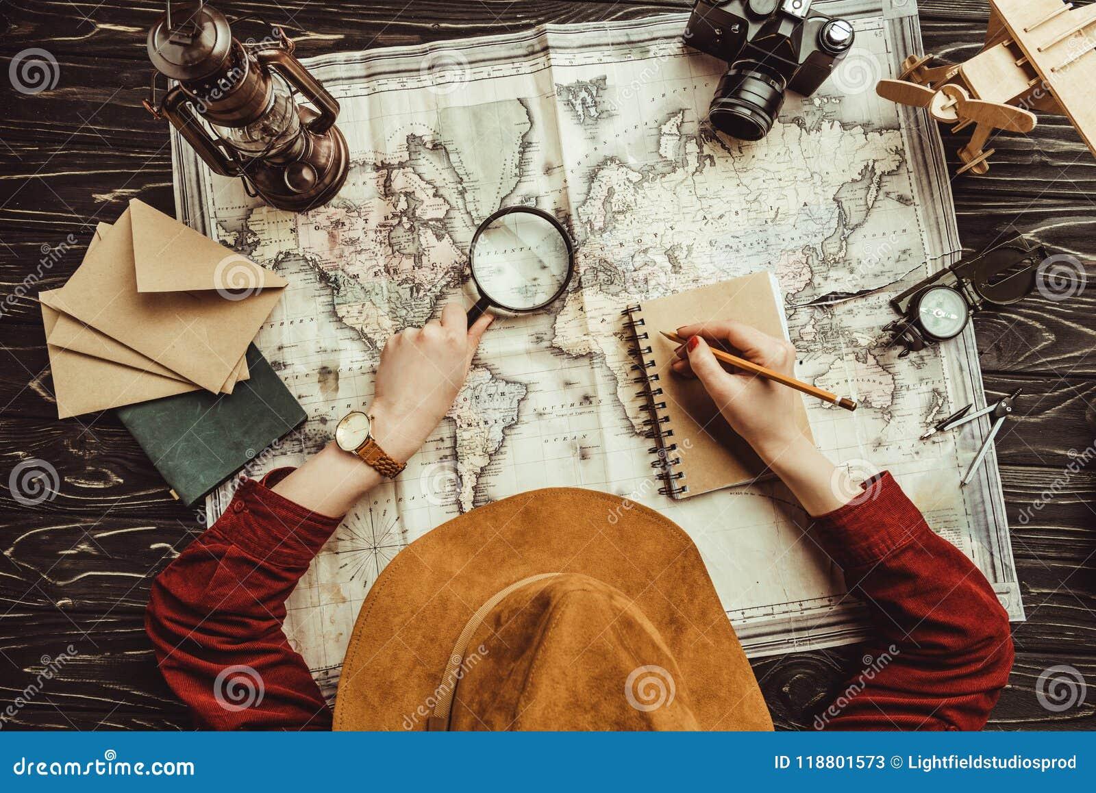 över huvudet sikt av kvinnadanandeanmärkningar i anteckningsbok med den tomma kuvert-, översikts- och fotokameran