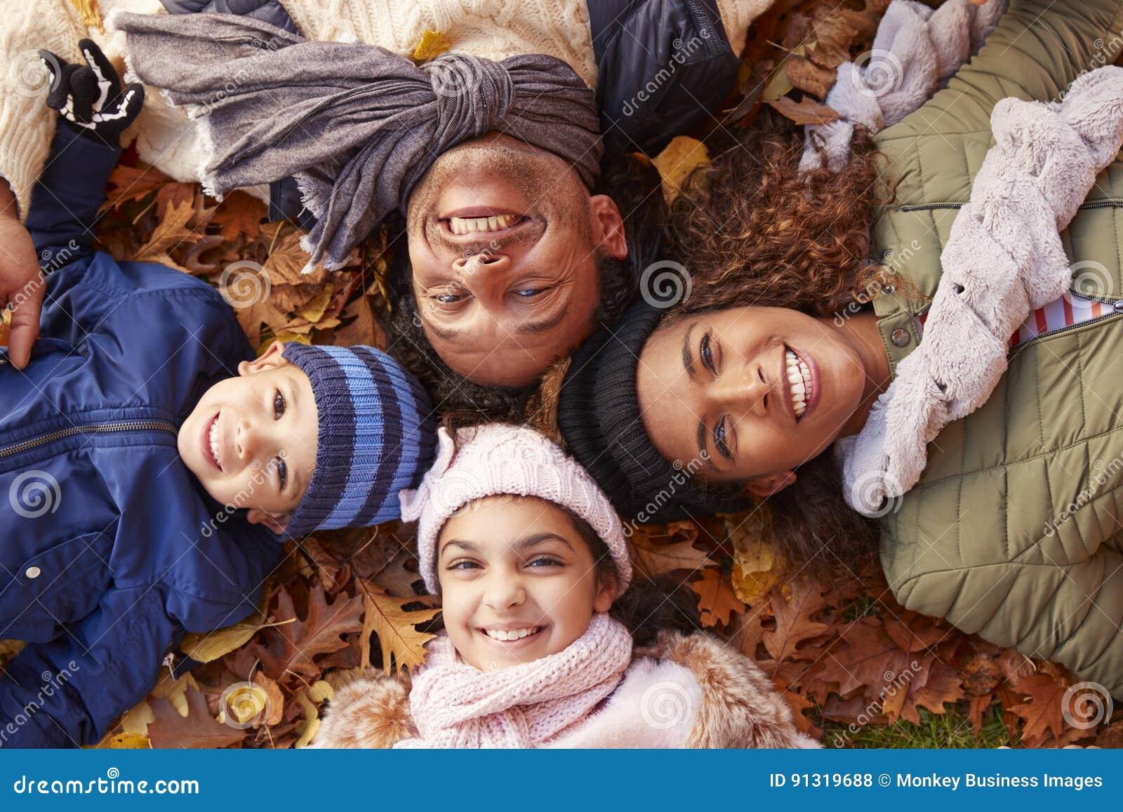 Över huvudet stående av familjen som ligger i Autumn Leaves