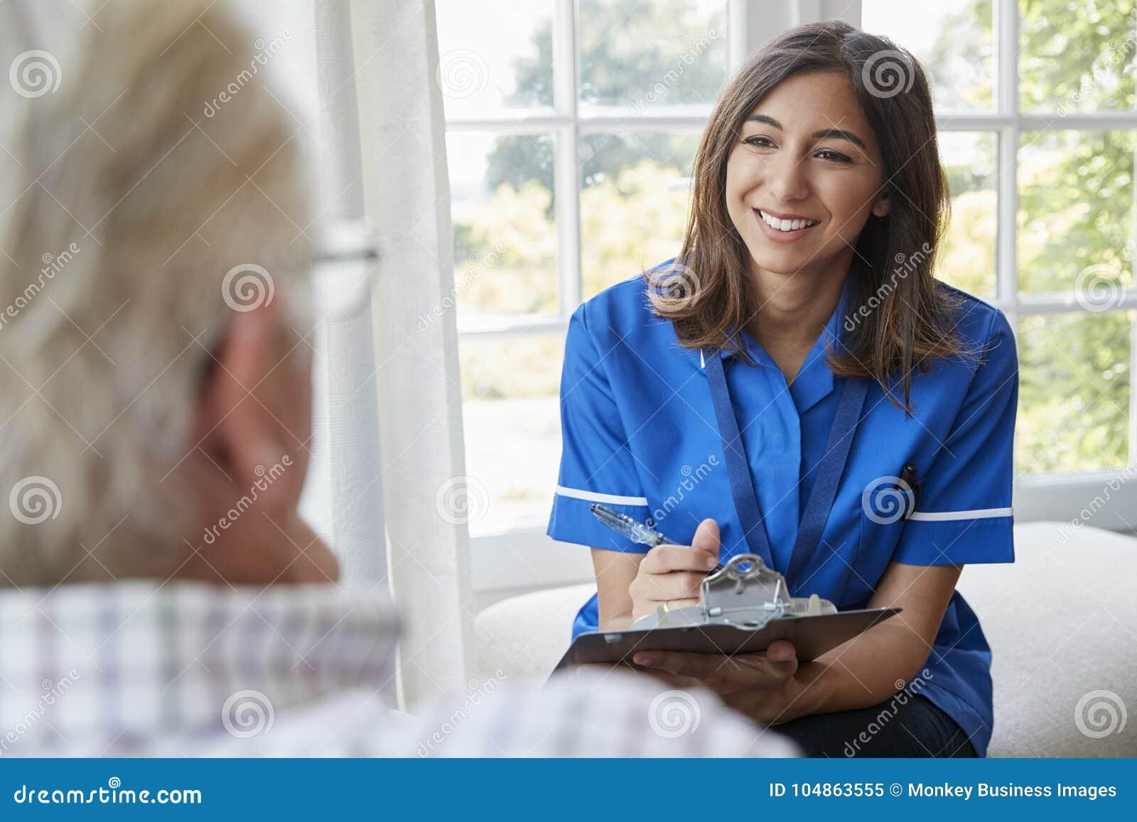 Över skuldrasikt av sjuksköterskan på hem- besök med den höga mannen