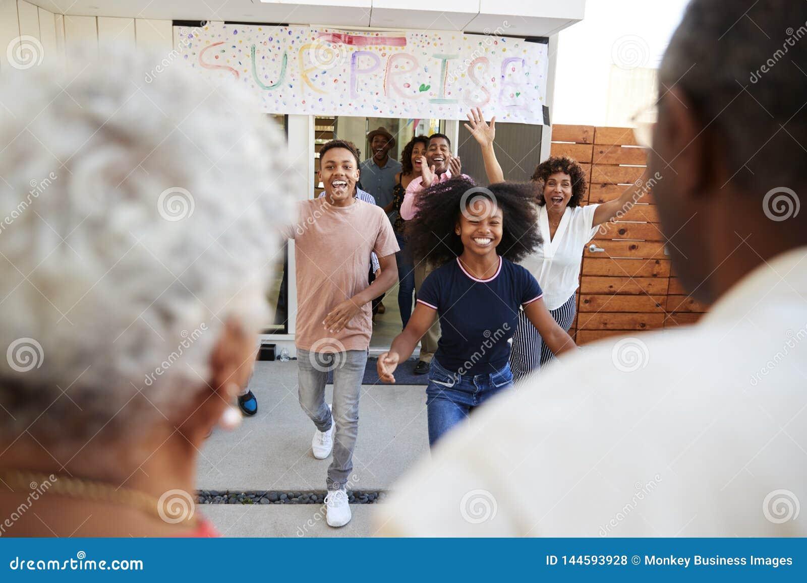 Över skuldrasikten av familjen som kör för att välkomna morföräldrar för ett överraskningfamiljparti