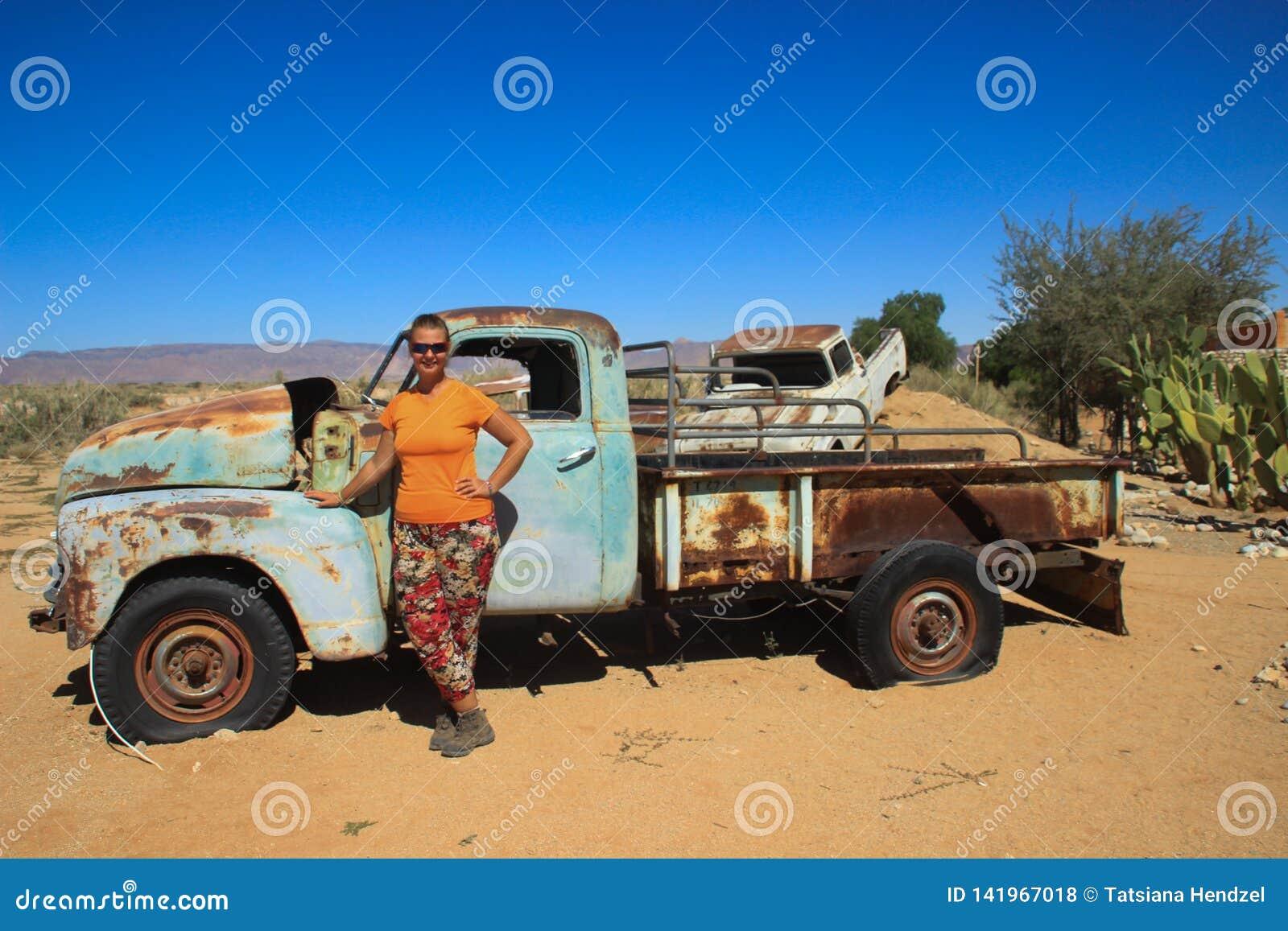 Övergav gamla rostiga bilar i öknen av Namibia och en fyllig vit turist- flicka nära den Namib-Naukluft nationalparken
