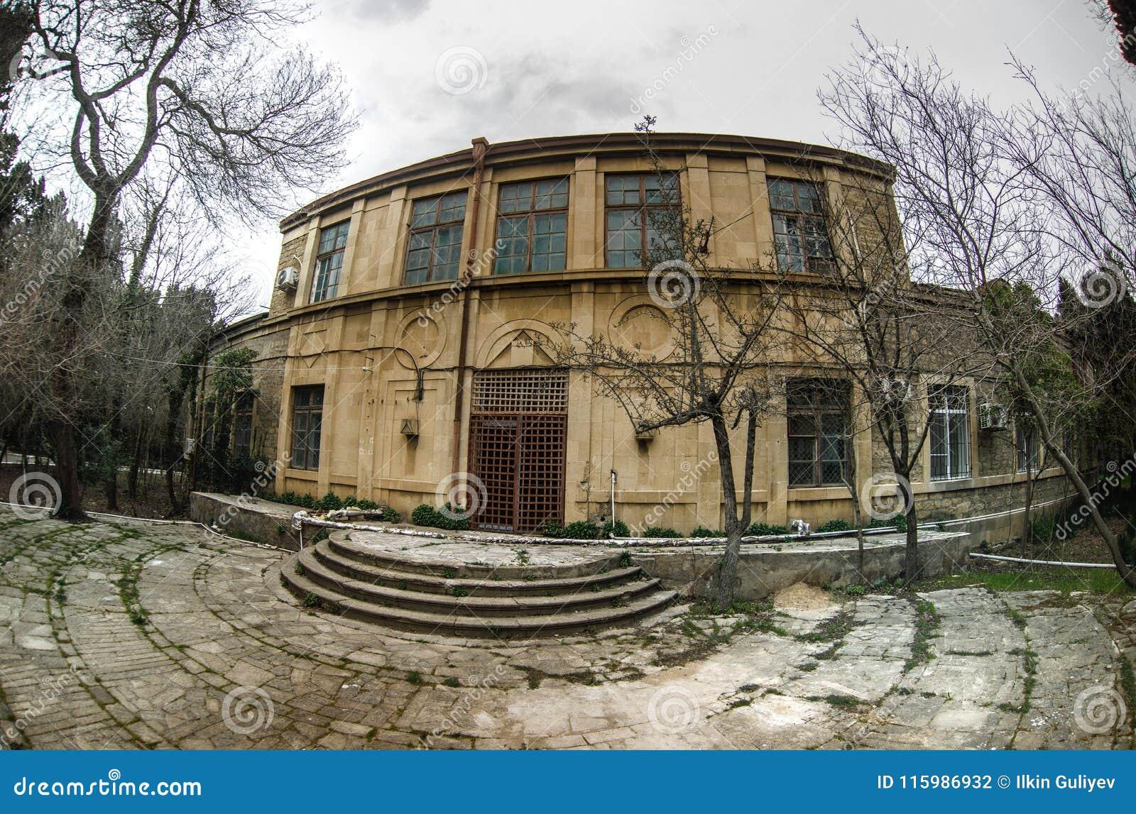 Övergiven byhusbyggnad i den Baku Botanical trädgården Inget i parkera med träd Vår