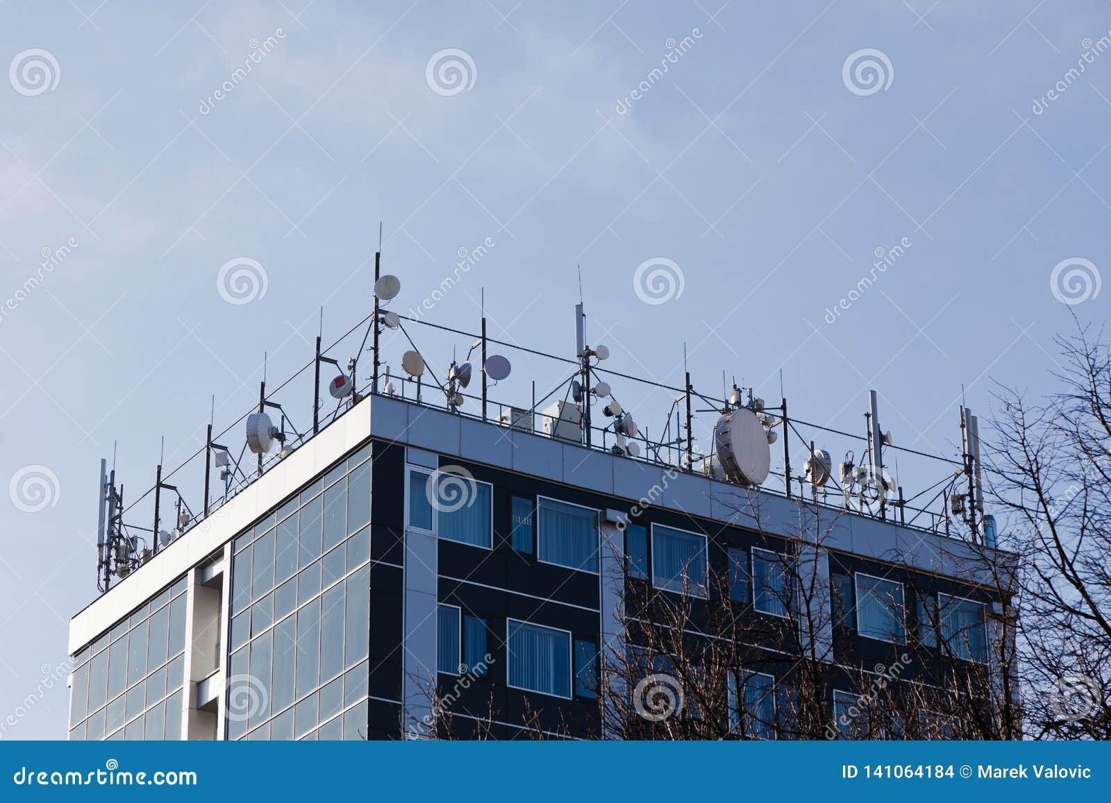 Överkant av byggnad som är full av satelliter och mikrovåganslutningar - staget trimmade