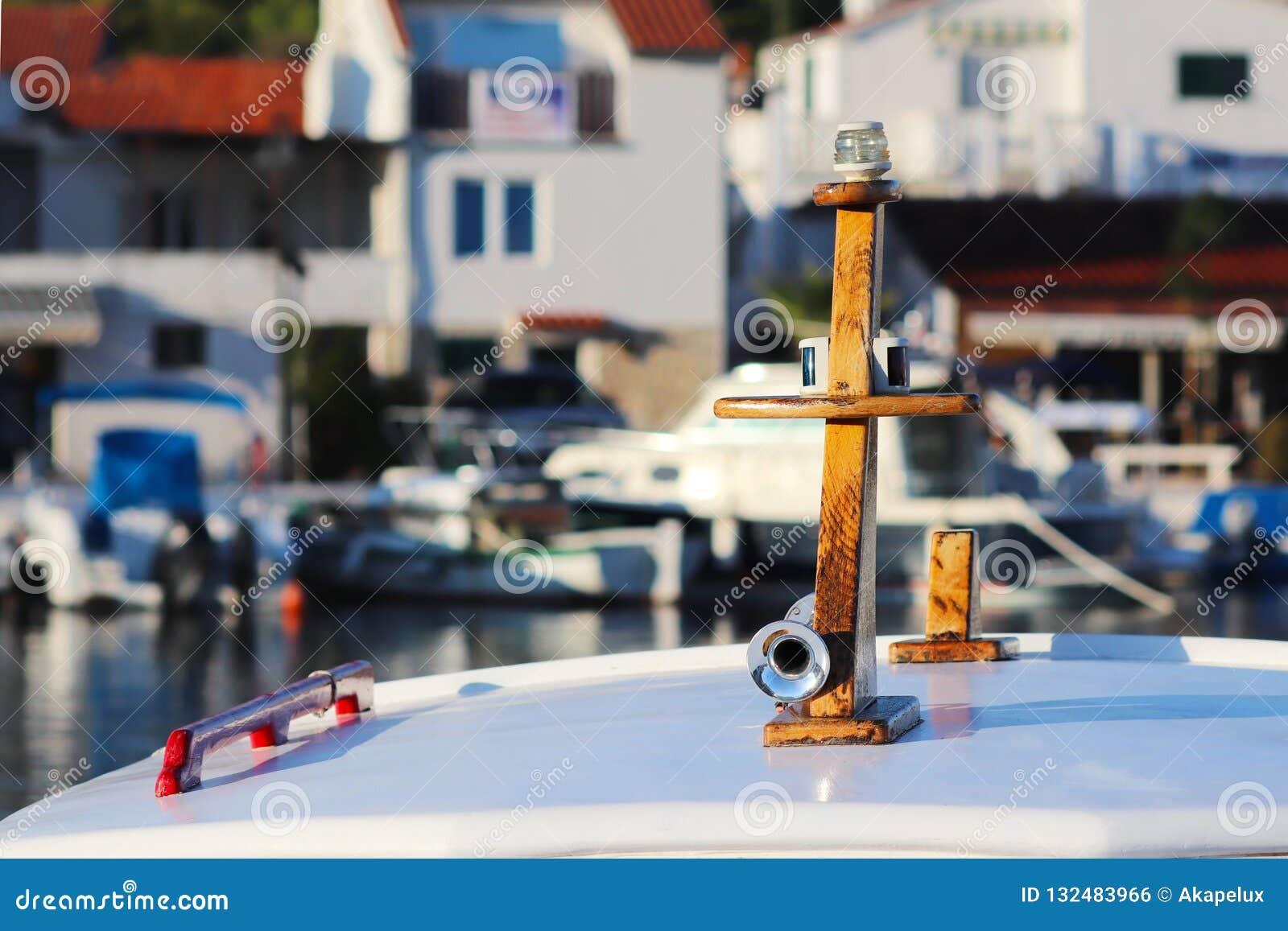 Överkant av en liten fiskebåt som utrustas med en siren och onboard navigeringljus Fragment av en havsskyttel på en dunkel bakgru