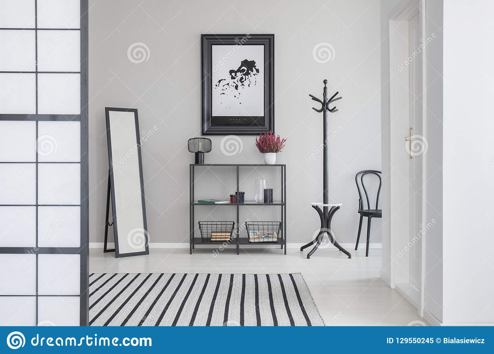 Översikt i svart ram på den gråa väggen av korridoren med spegeln, hyllan, hängaren och hår
