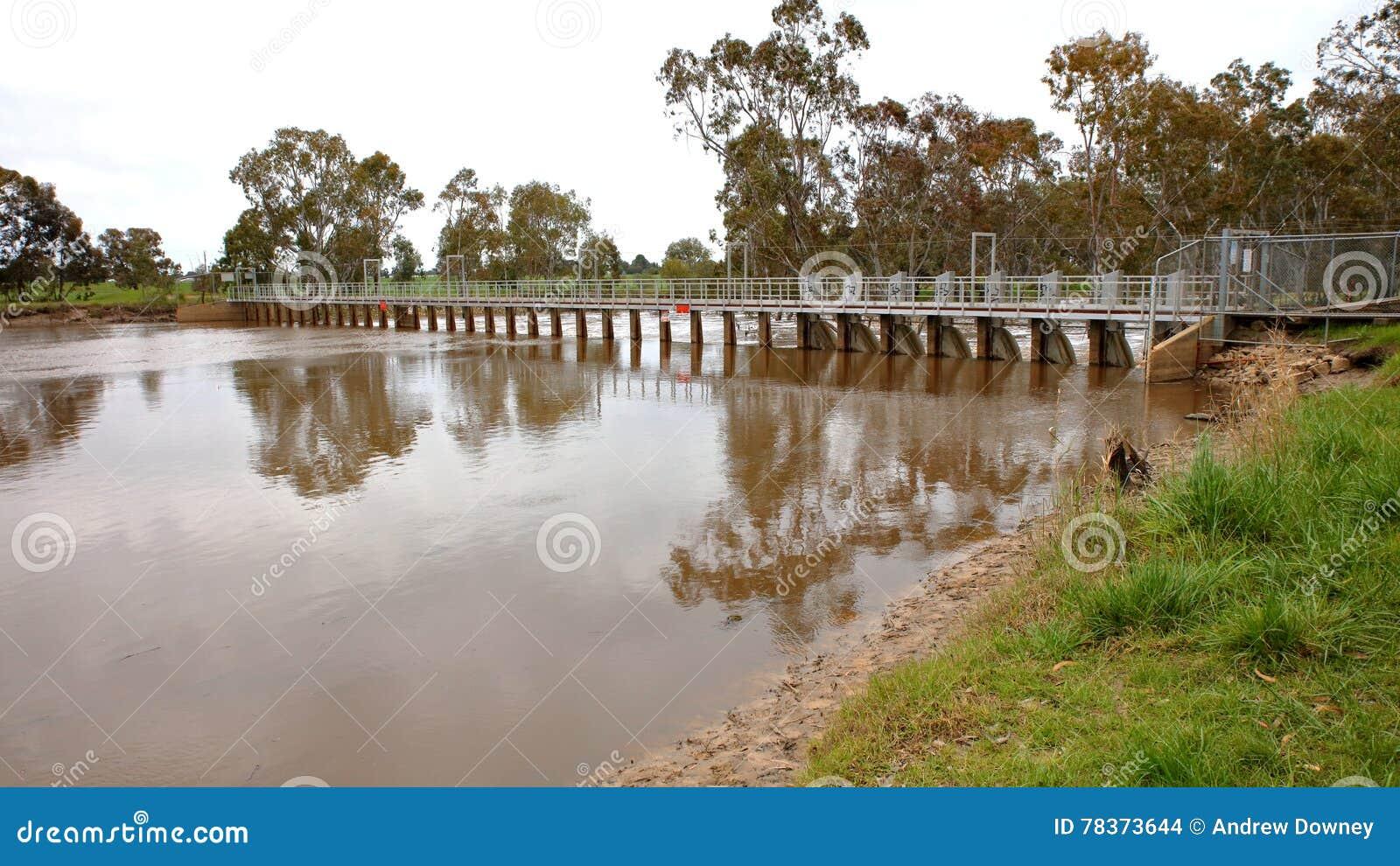 Översvämmad flod över dammbyggnaden