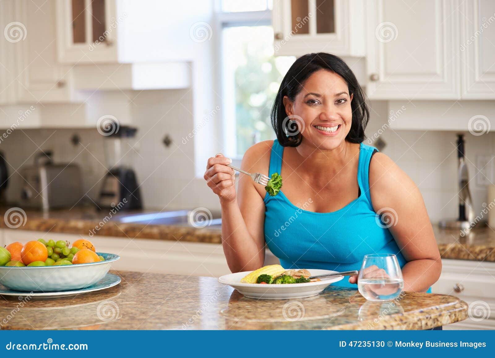 Överviktig kvinna som äter sunt mål i kök