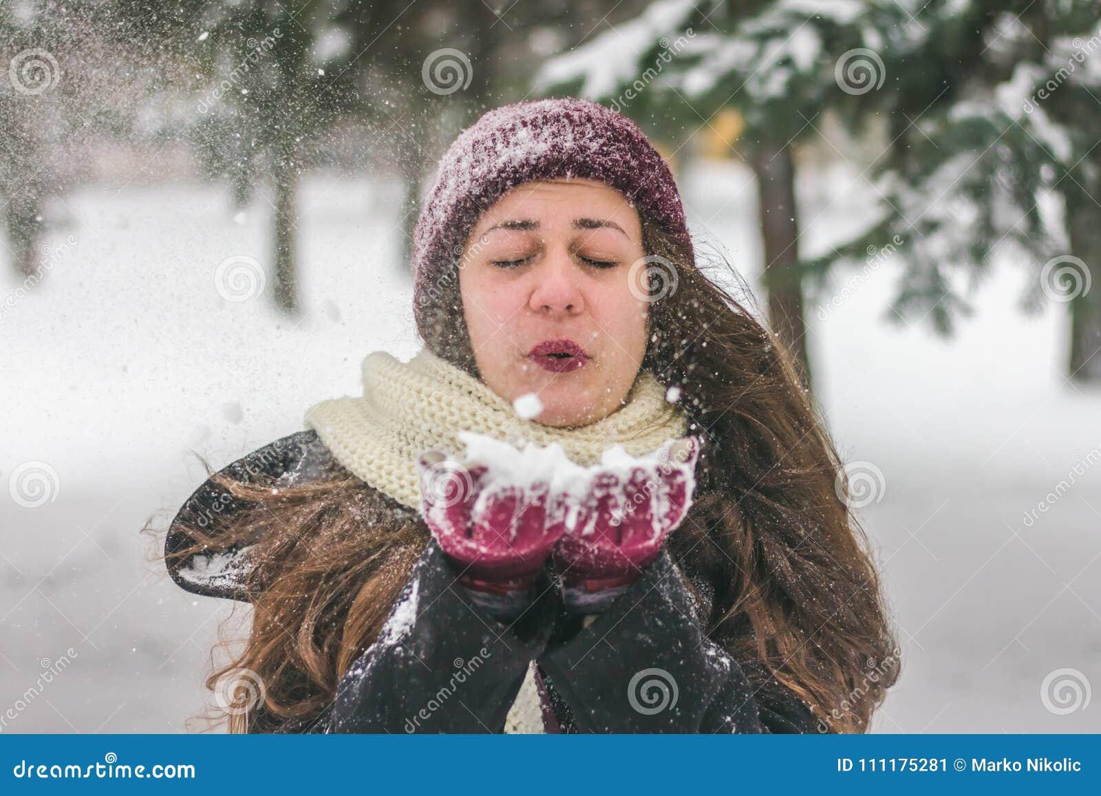 Övervintra flickan med en röd hatt som blåser snö