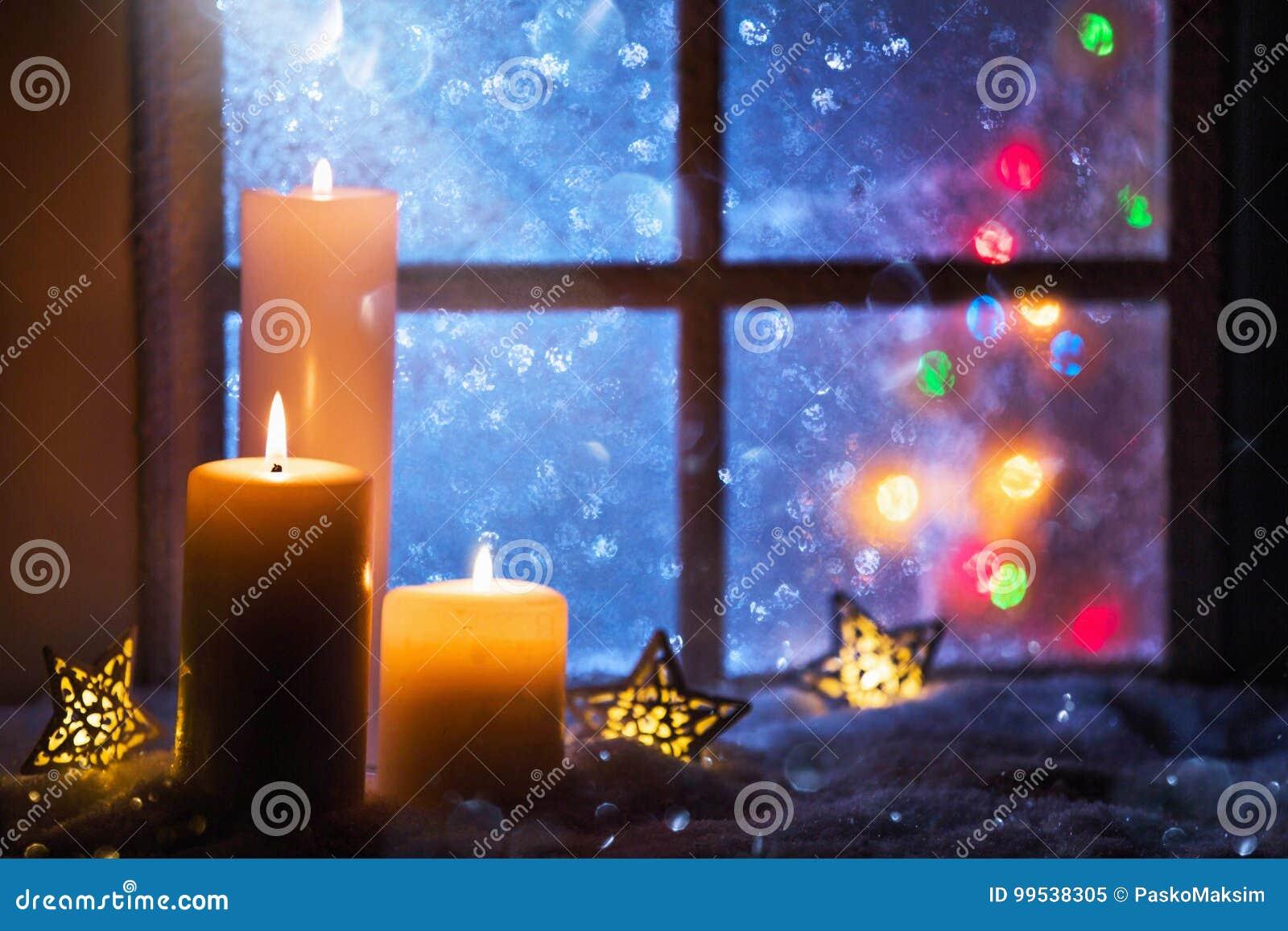 Övervintra garnering med stearinljus nära dettäckte fönstret