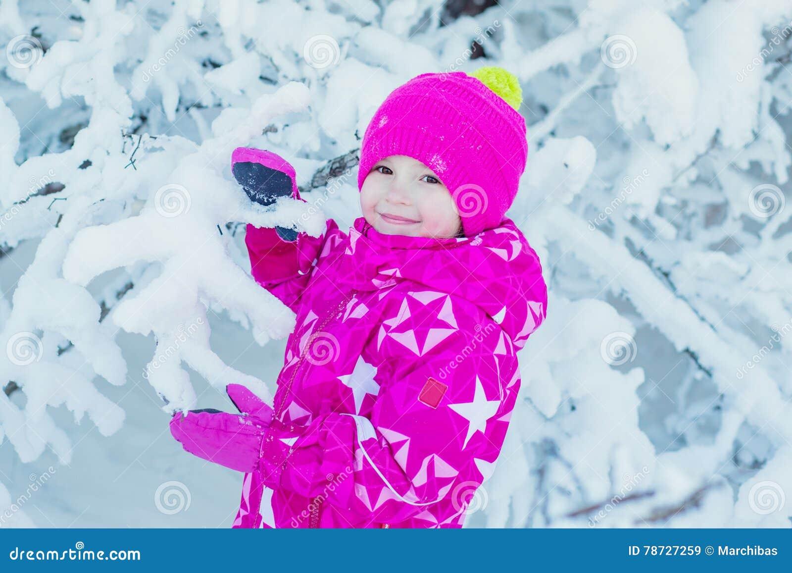 Övervintra ståenden av en gullig liten flicka i snön