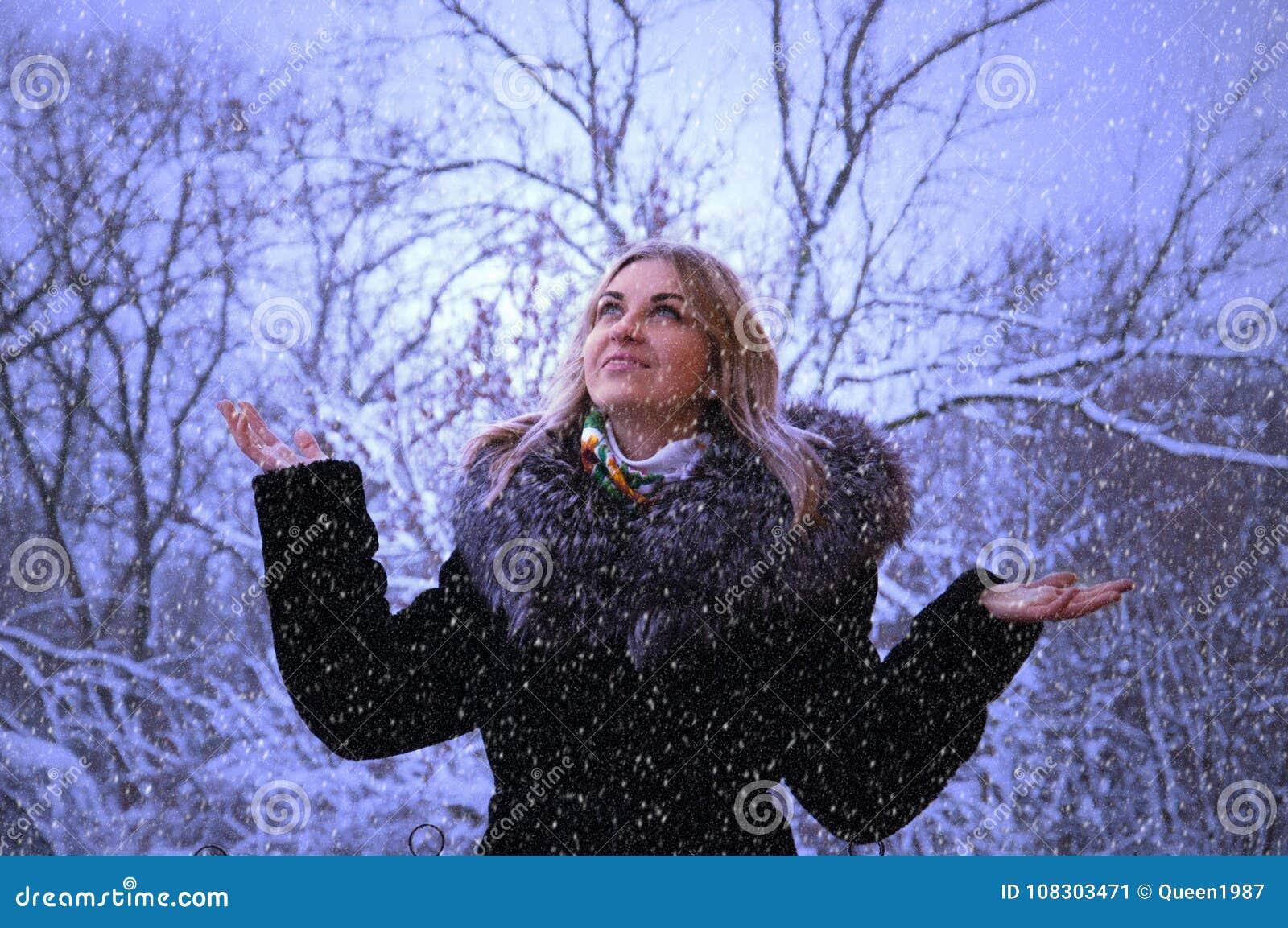 Övervintra ståenden av en lycklig ung kvinna som går i natur i snön