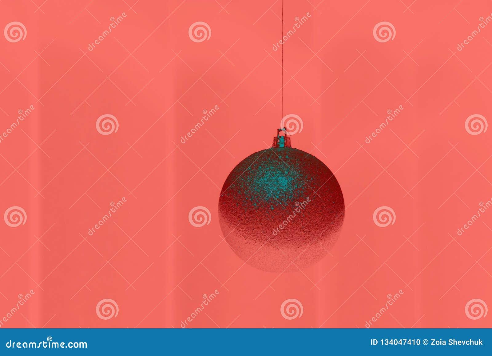 Única bola do Natal no fundo na cor do ano 2019 Pantone - coral de vida