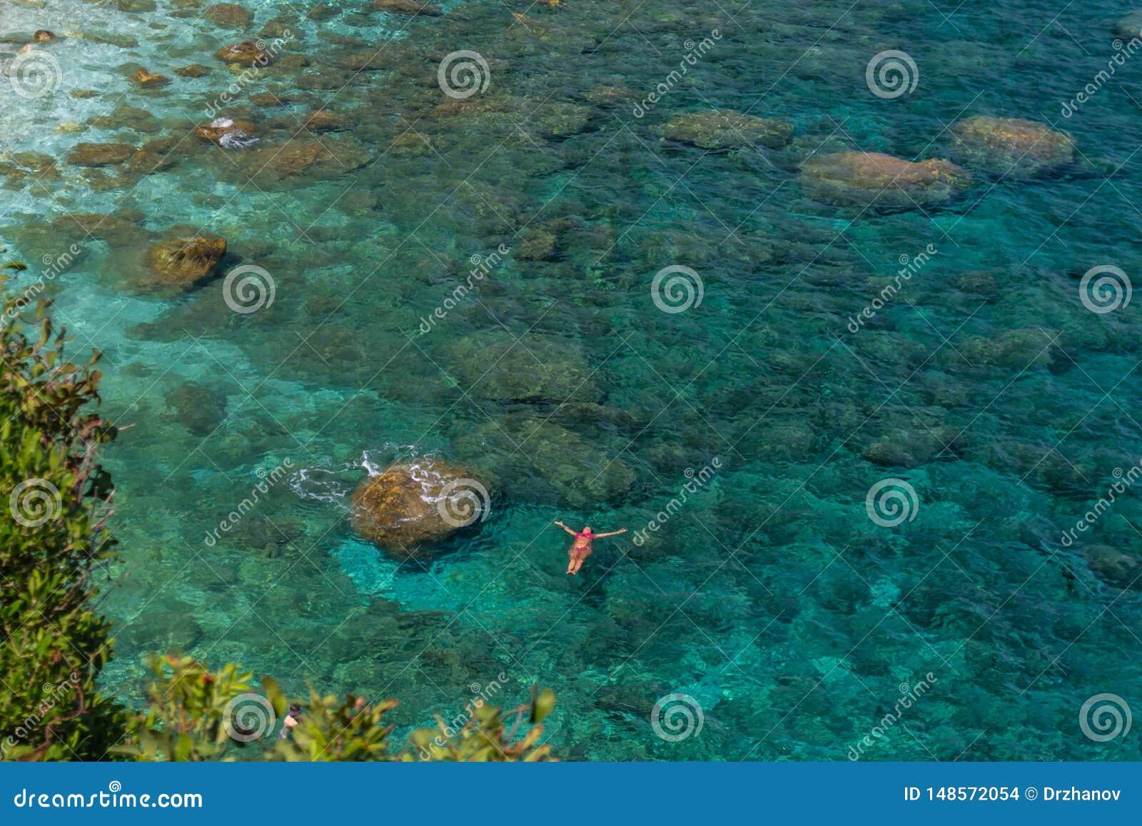 A única mulher coloca na água claro de água-marinha bonita no abrandamento, vista superior da altura