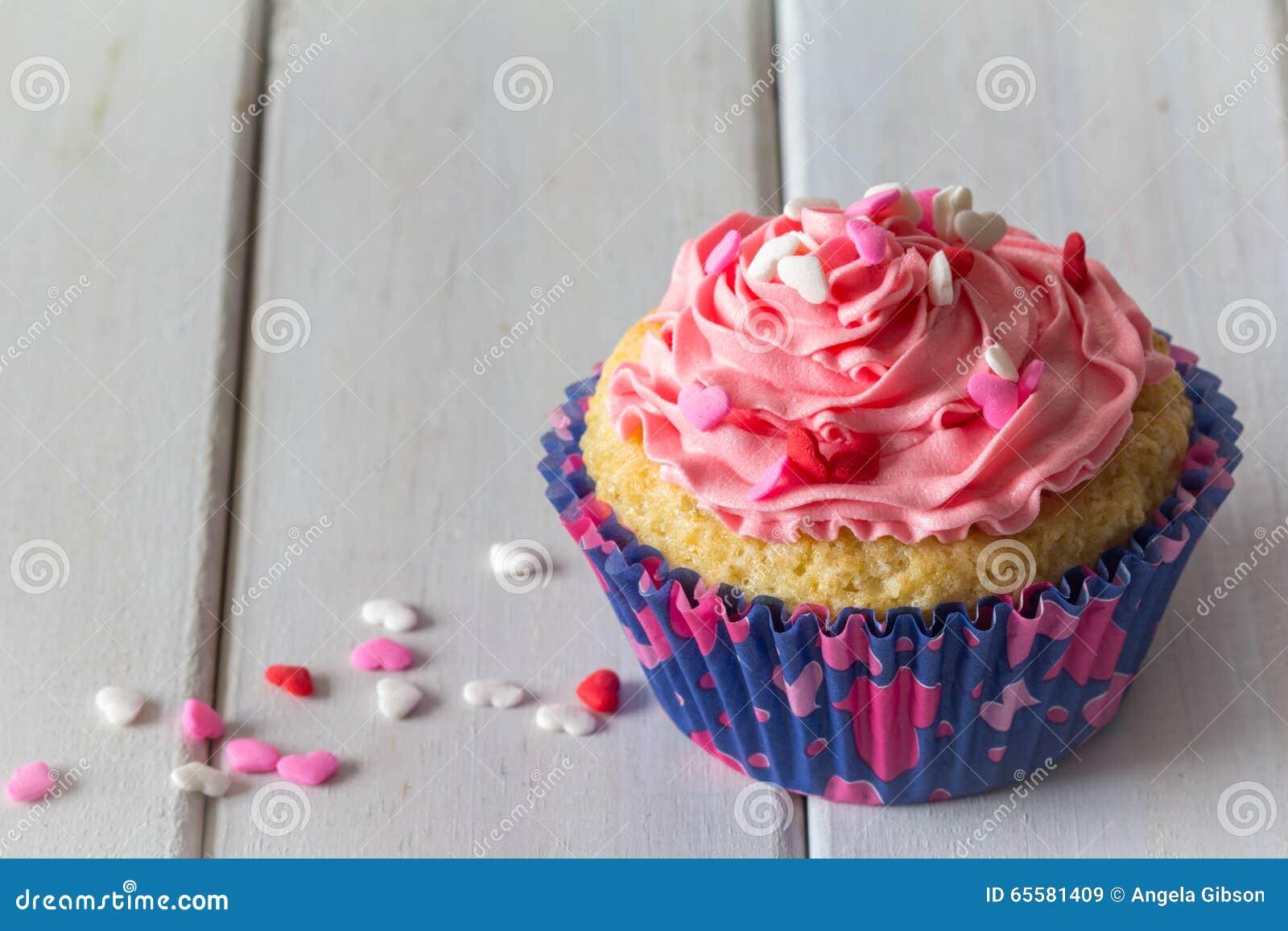 Único queque e geada cor-de-rosa na tabela com espaço da cópia acima do vertical