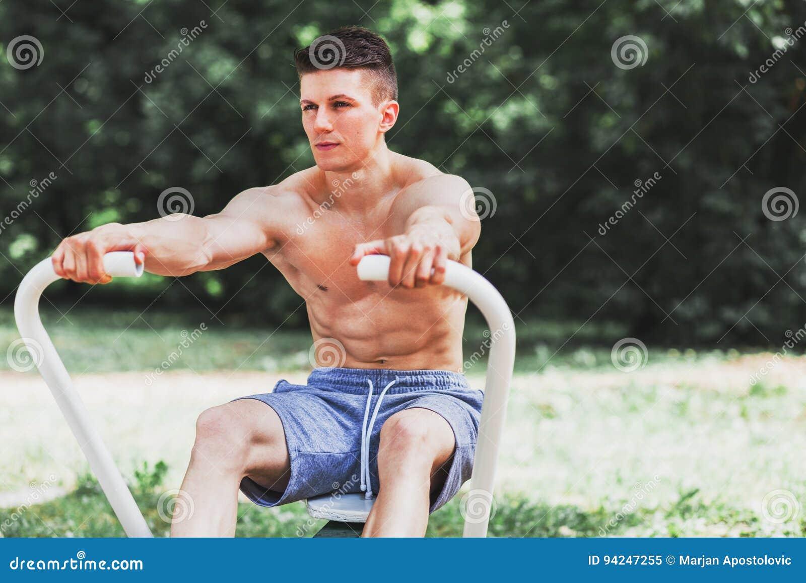 Übendes Rudern des jungen muskulösen Mannes