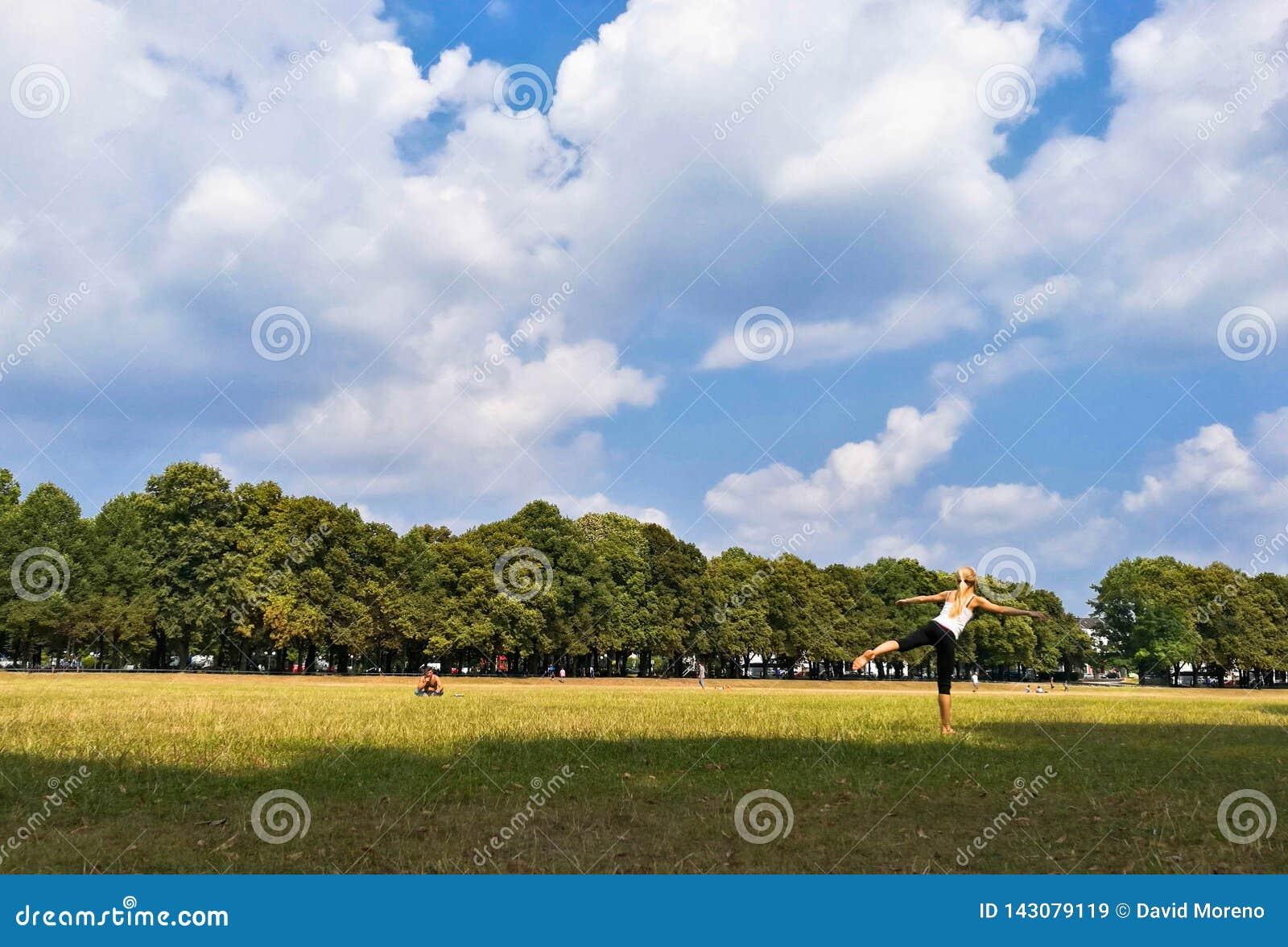 übendes Yoga der Frau im Freien im Park an einem sonnigen Tag