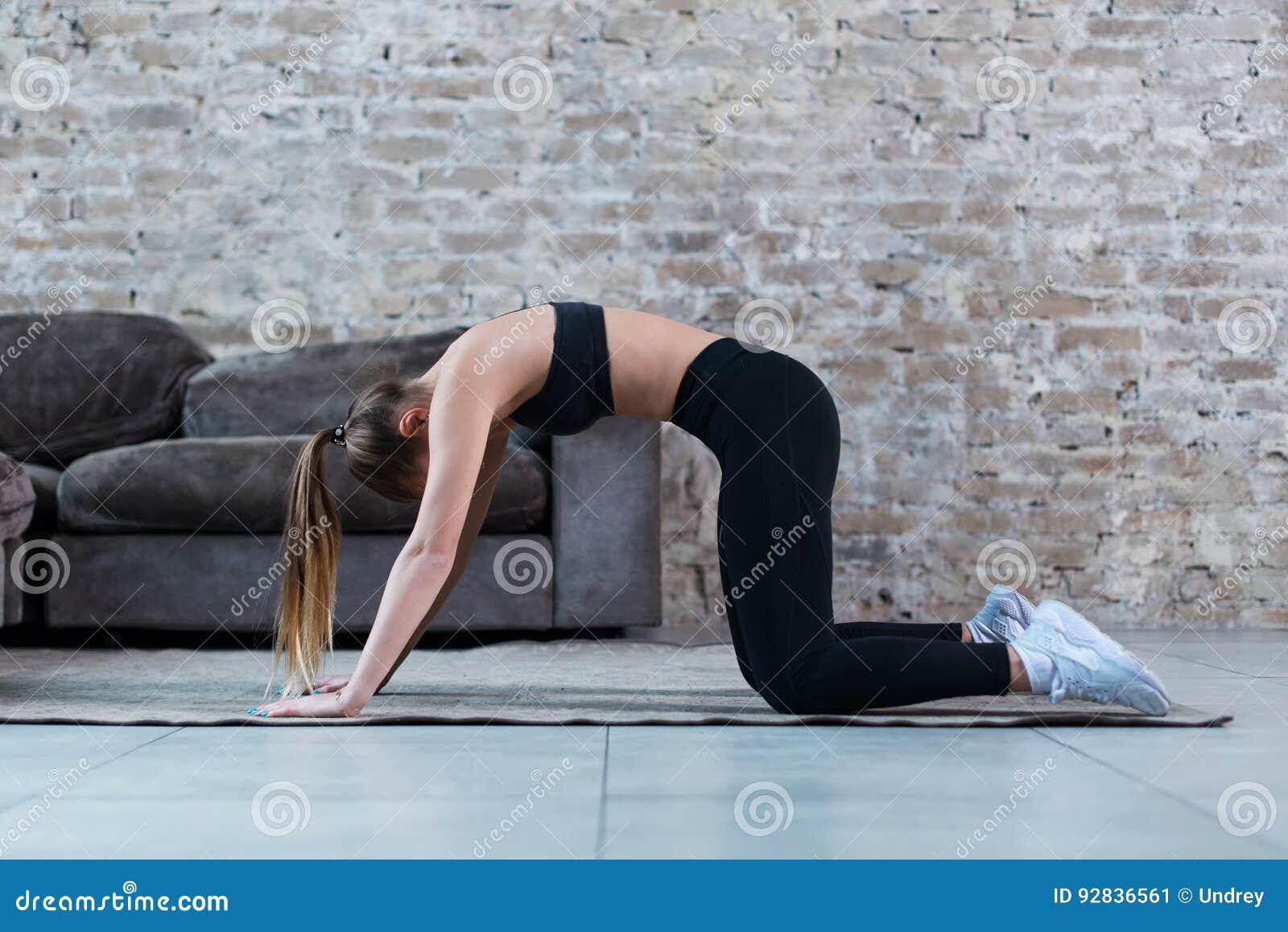 Übendes Yoga der geeigneten jungen kaukasischen Frau zu Hause, das in der Katzen- und Kuhhaltung zurück wölbt sie steht