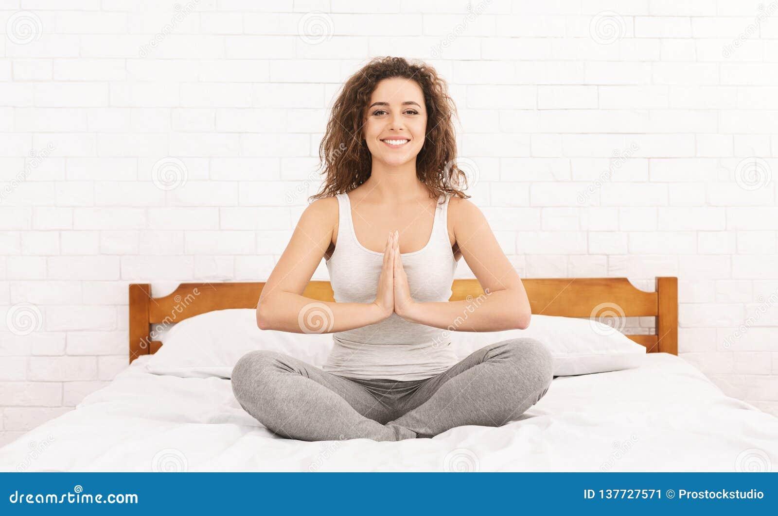 Übendes Yoga der jungen kaukasischen Frau im Bett