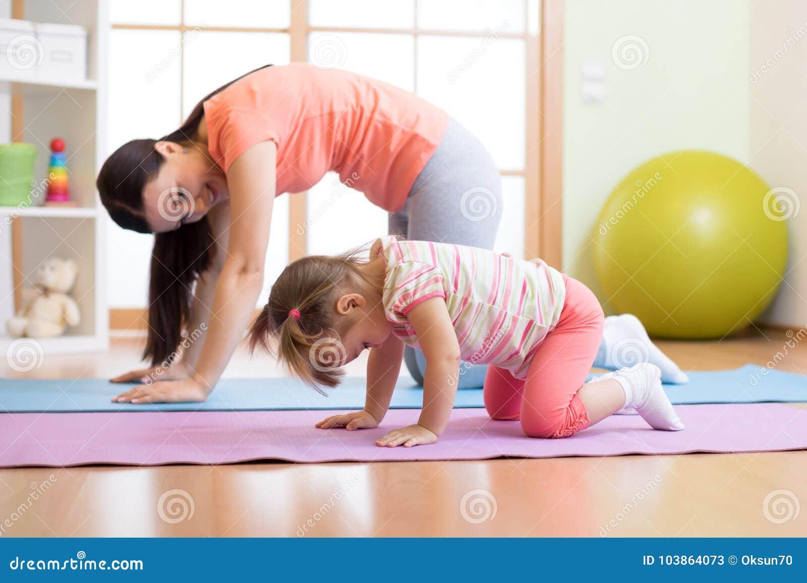 Übendes Yoga der Mutter- und Kindertochter zusammen zu Hause Sport und Familienkonzept
