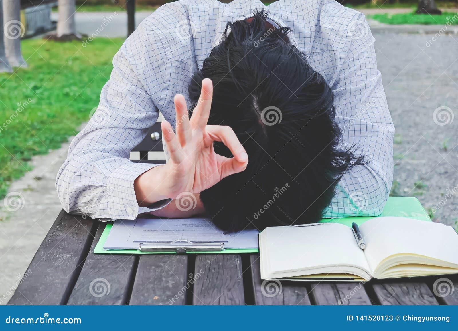 Überarbeiteter, müder Geschäftsmann im Büro schlafend an seinem Schreibtischarbeiten über einem Buch, nachdem er den ganzen Tag a