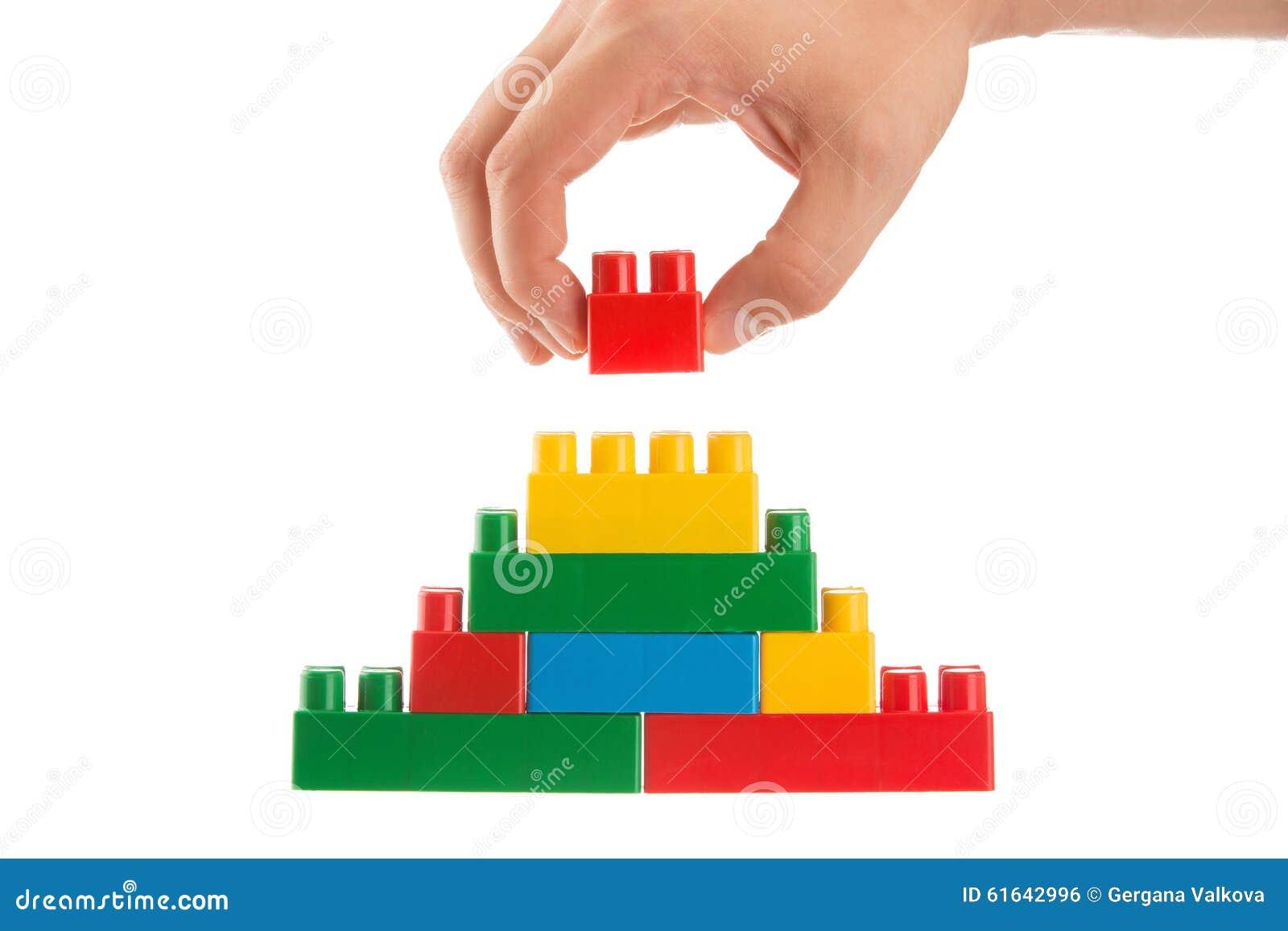 Übergeben Sie das Aufbauen einer Wand, indem Sie herauf lego, Geschäftskonzeption stapeln